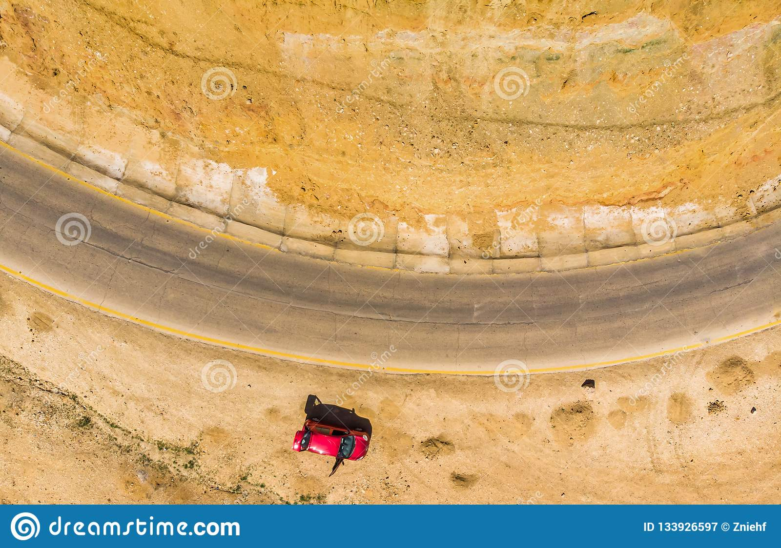 Vertical aerial photograph of the cliffs and the road at the Dead Sea in Jordan, with a parked red car. taken with the drone