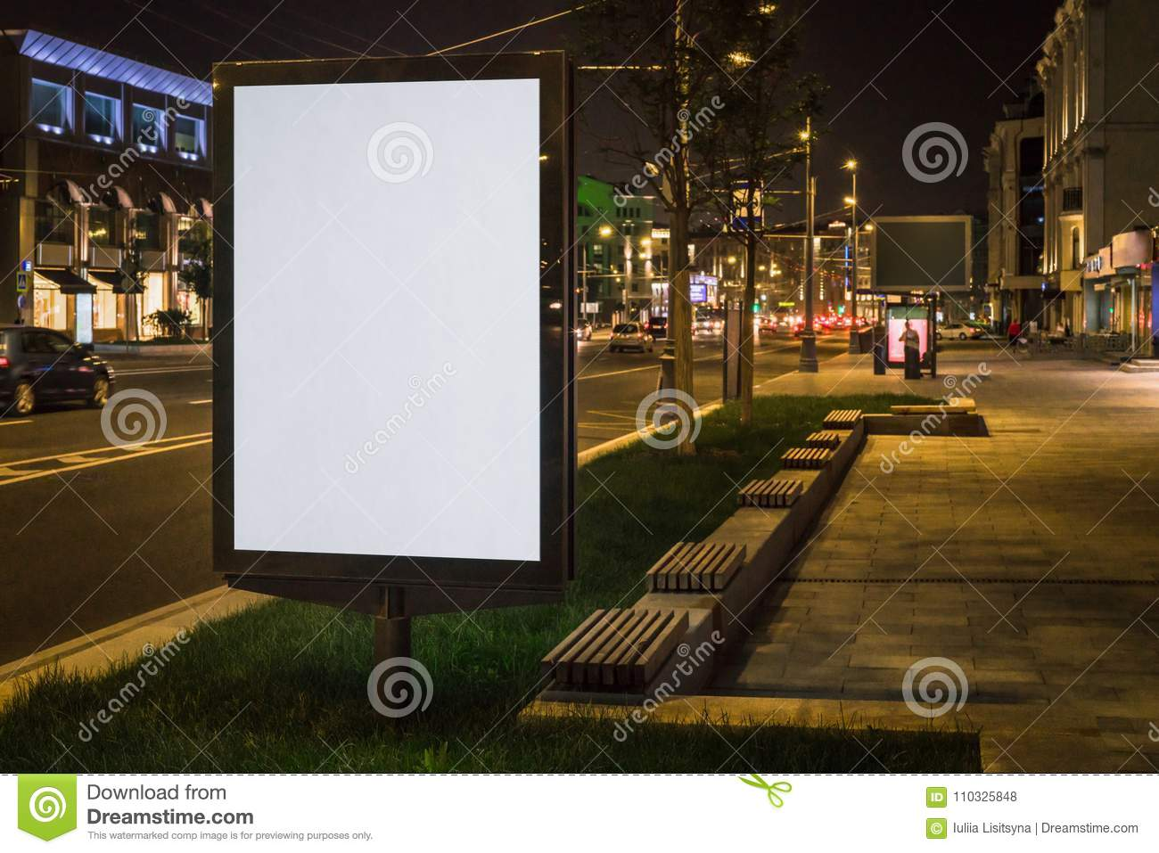 Vertical blank glowing billboard on night city street. In background buildings and road with cars. Mock up.