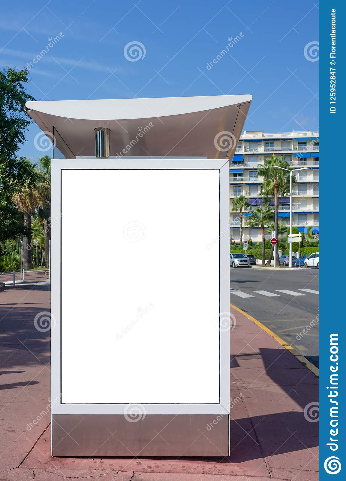 Vertical blank white billboard at bus stop on city street. In the background buildings and road. Mock up. Poster on street