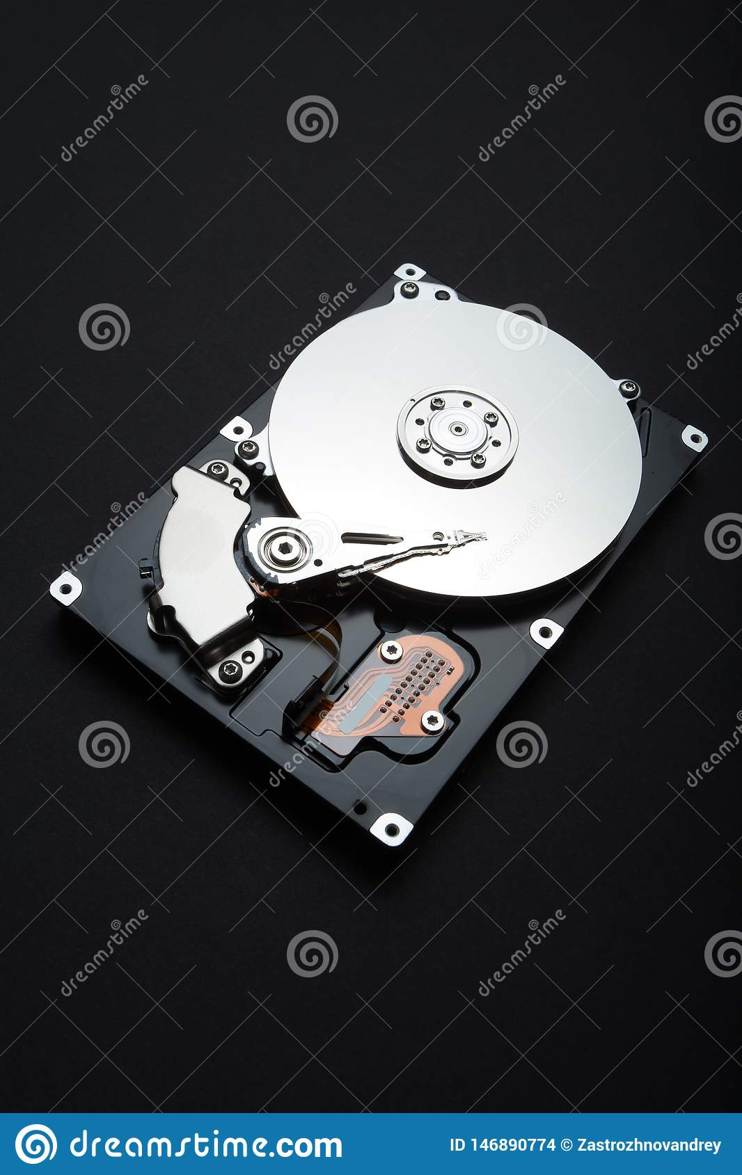 Vertical close up of hard disk with white reflection on black background