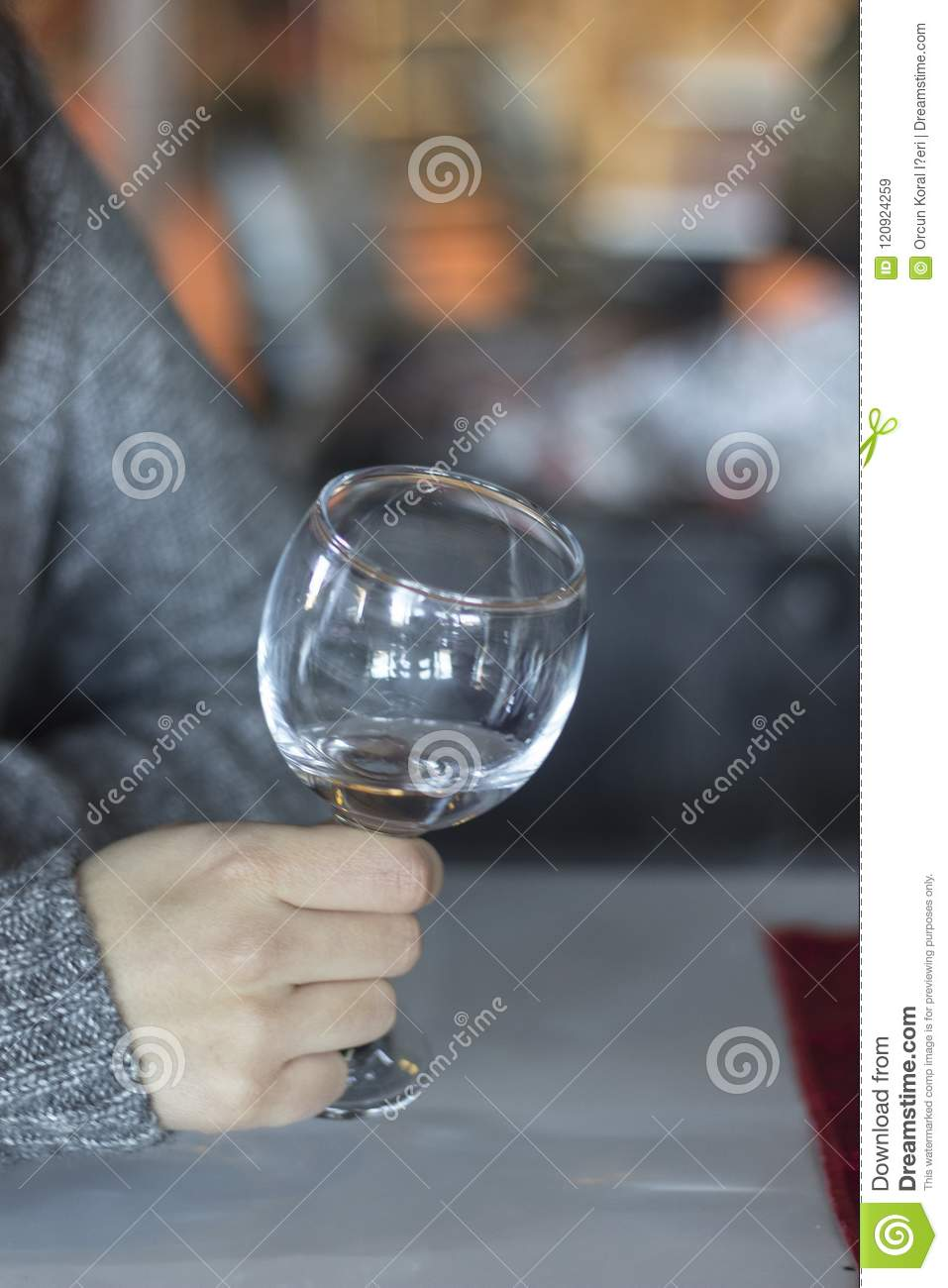Vertical close-up shot for woman holds empty wine glass with blurry background in Izmir at Turkey for winter season