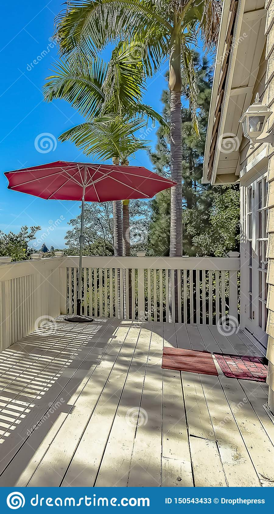 Vertical frame Balcony overlooking houses and trees against bright blue sky on a sunny day