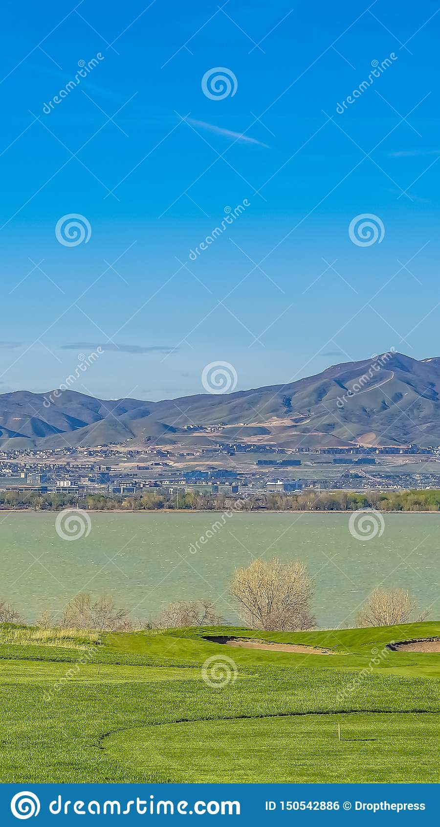 Vertical frame Mountain towering over a vast valley and lake under bright blue sky