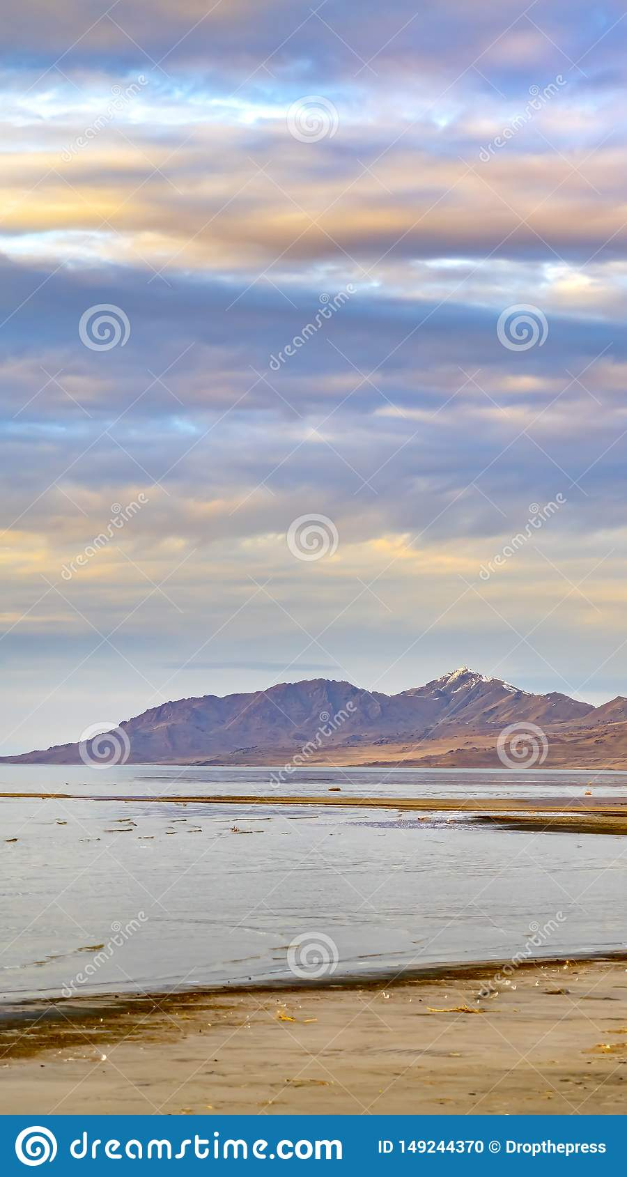 Vertical frame Panorama of a calm lake with vast sandy shore under cloud filled sky