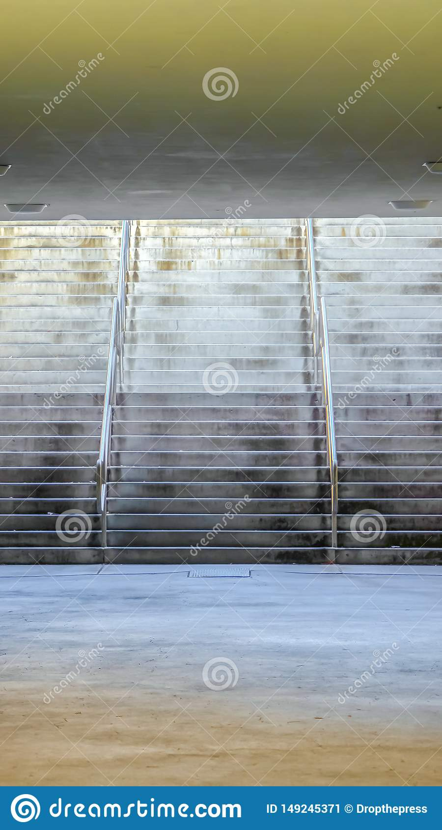 Vertical frame Wide flight of stairs at a passageway under a building with brick wall