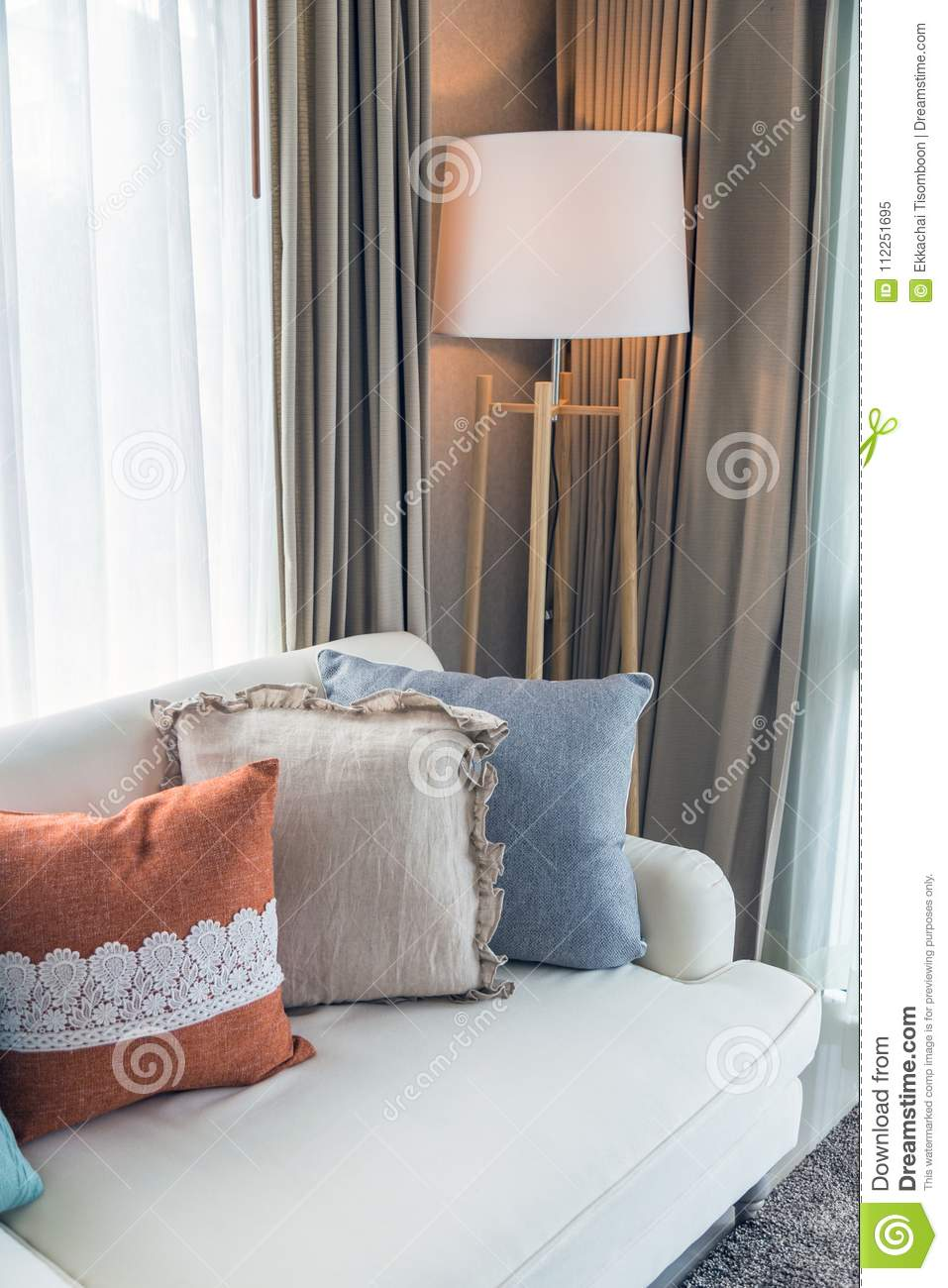 Colorful Pillows On Beige Sofa With Lamp In Livingroom