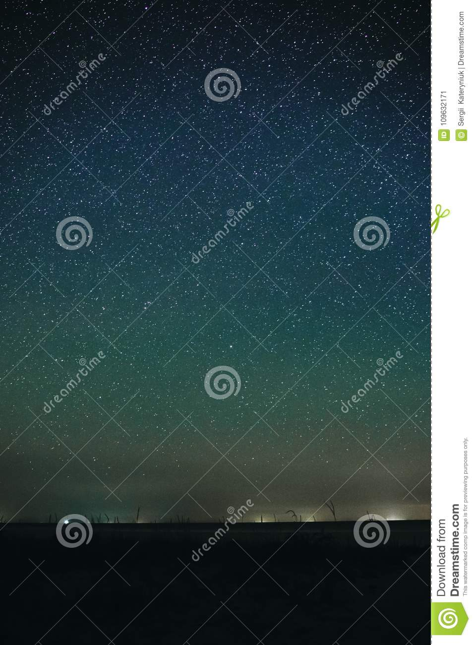 Vertical landscape of bright starry night sky with lights upon on it and sandy empty beach with grass and ocean