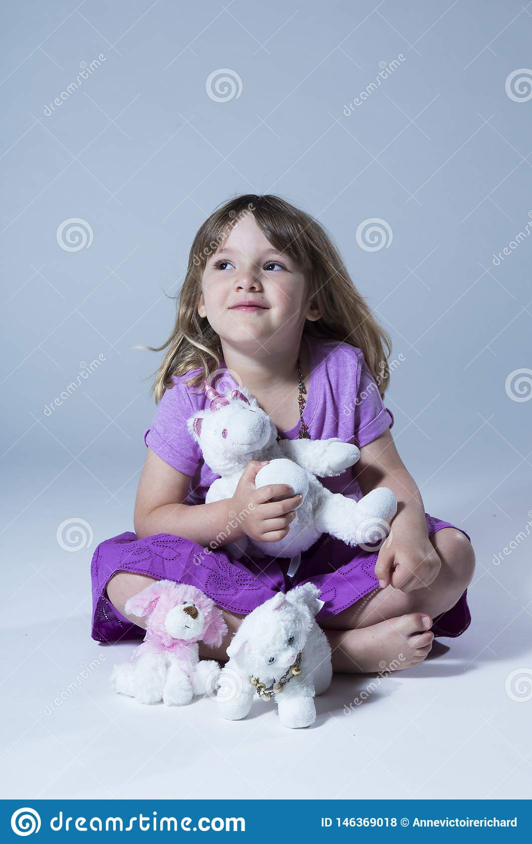 Vertical photo of cute little girl in mauve top and purple skirt sitting cross-legged