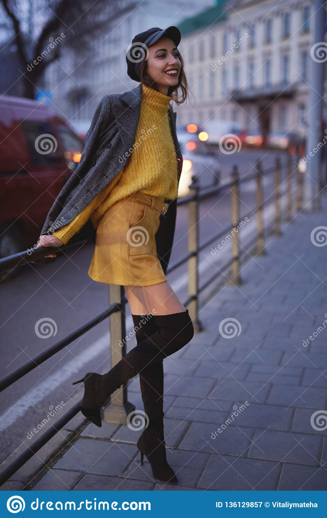 Beautiful fashionable woman in bright yellow sweater and skirt walking and posing outdoors