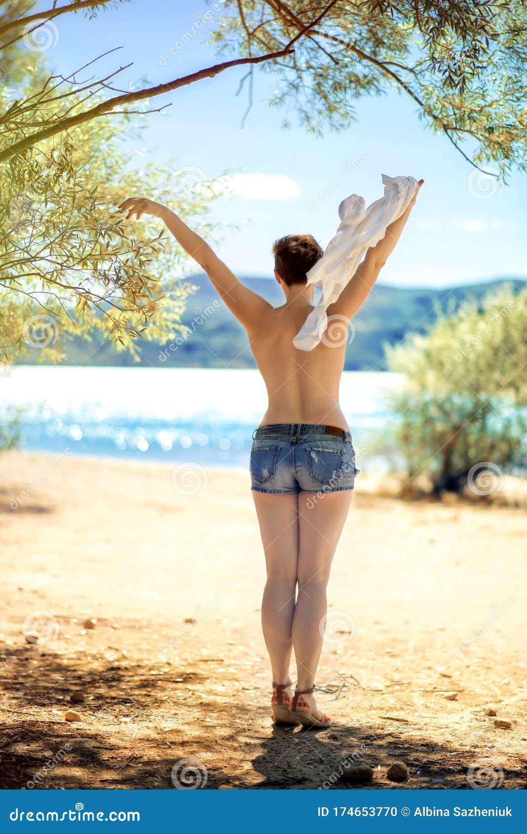 Young Beautiful Woman In White Short Tight Dress Posing