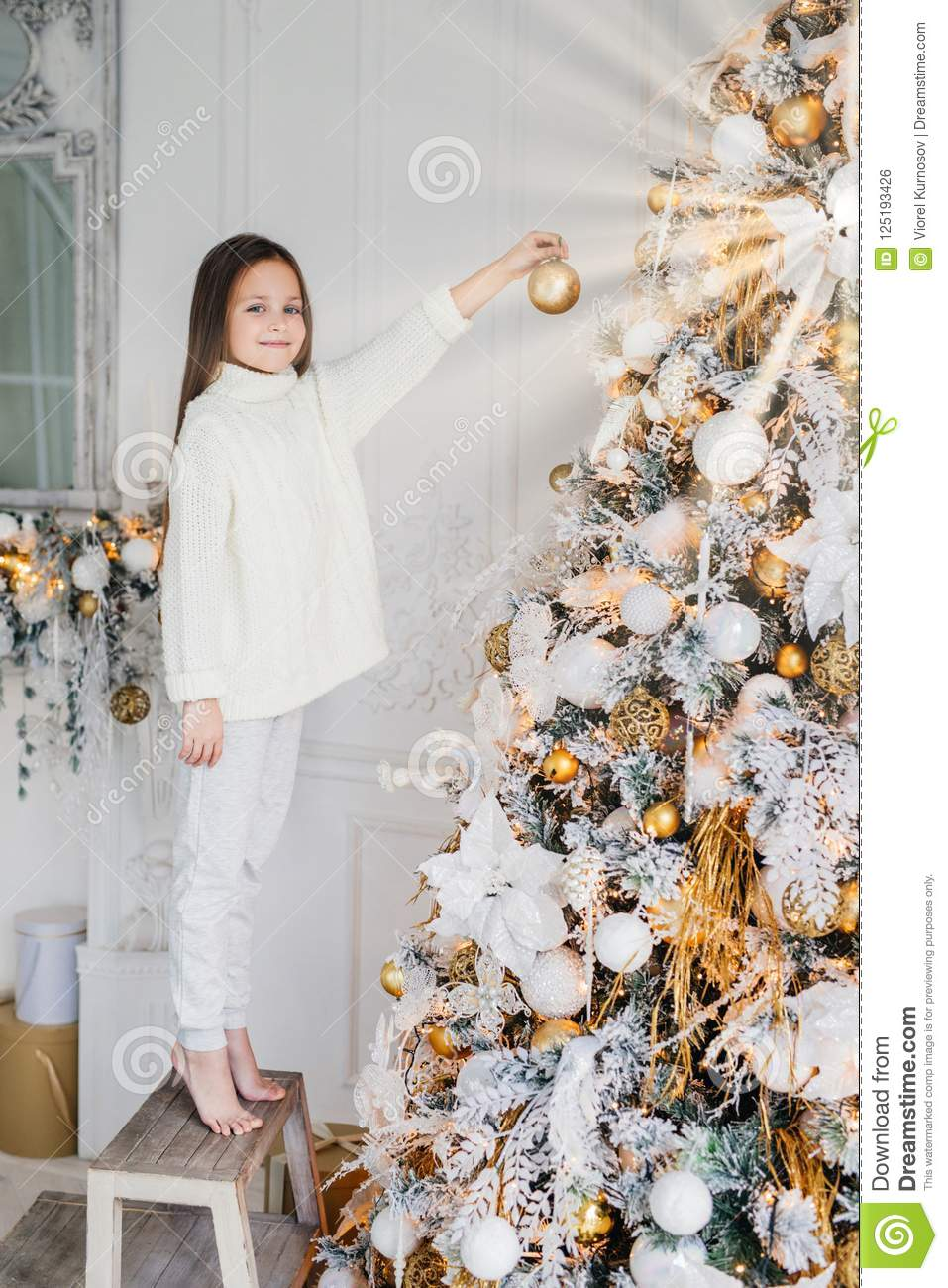 Vertical portrait of female child stands near New Year tree, holds decorated new year ball, decorates fir tree, has happy expressi
