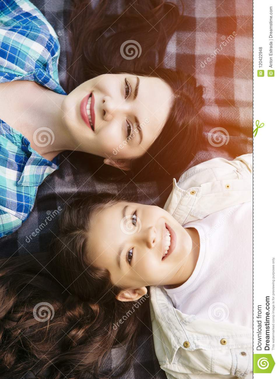 Vertical portrait of young woman and girl lying on blanket and looking on camera. They are smiling. Girls are beautiful