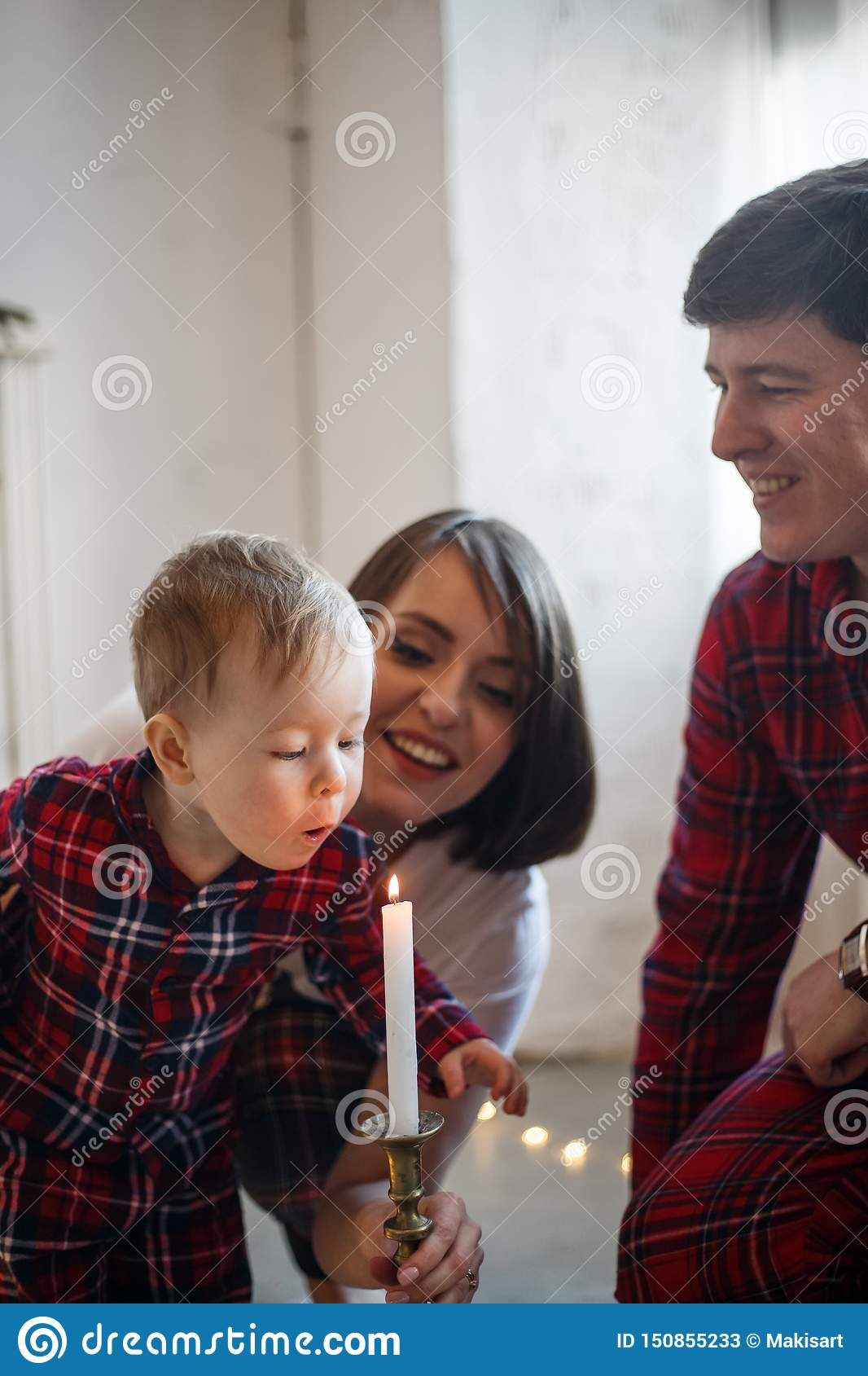 Vertical ppicture of family. Child is blowing to candle. Parents are looking at him and smiling
