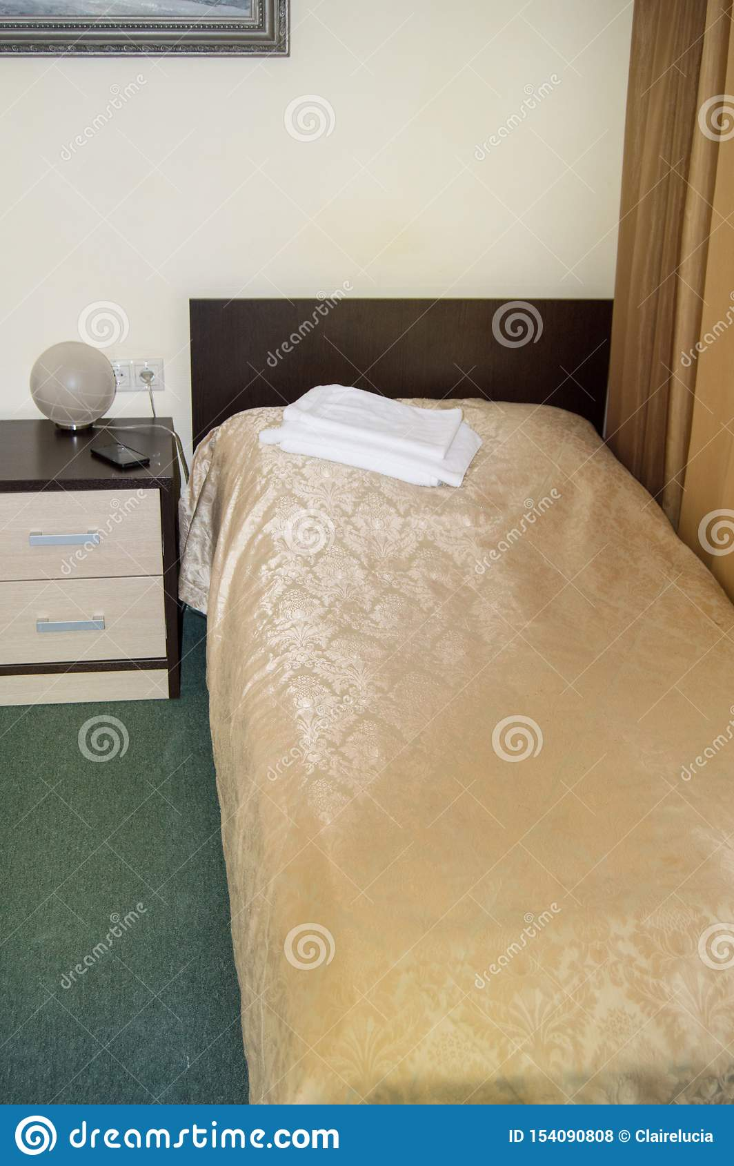 Vertical shot of the interior of the hotel bedroom with an empty single bed with wooden headboard and bedside table and towels on