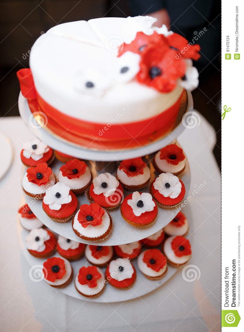 Vertical Shot Of A Red And White Wedding Cake With Small Cupcake