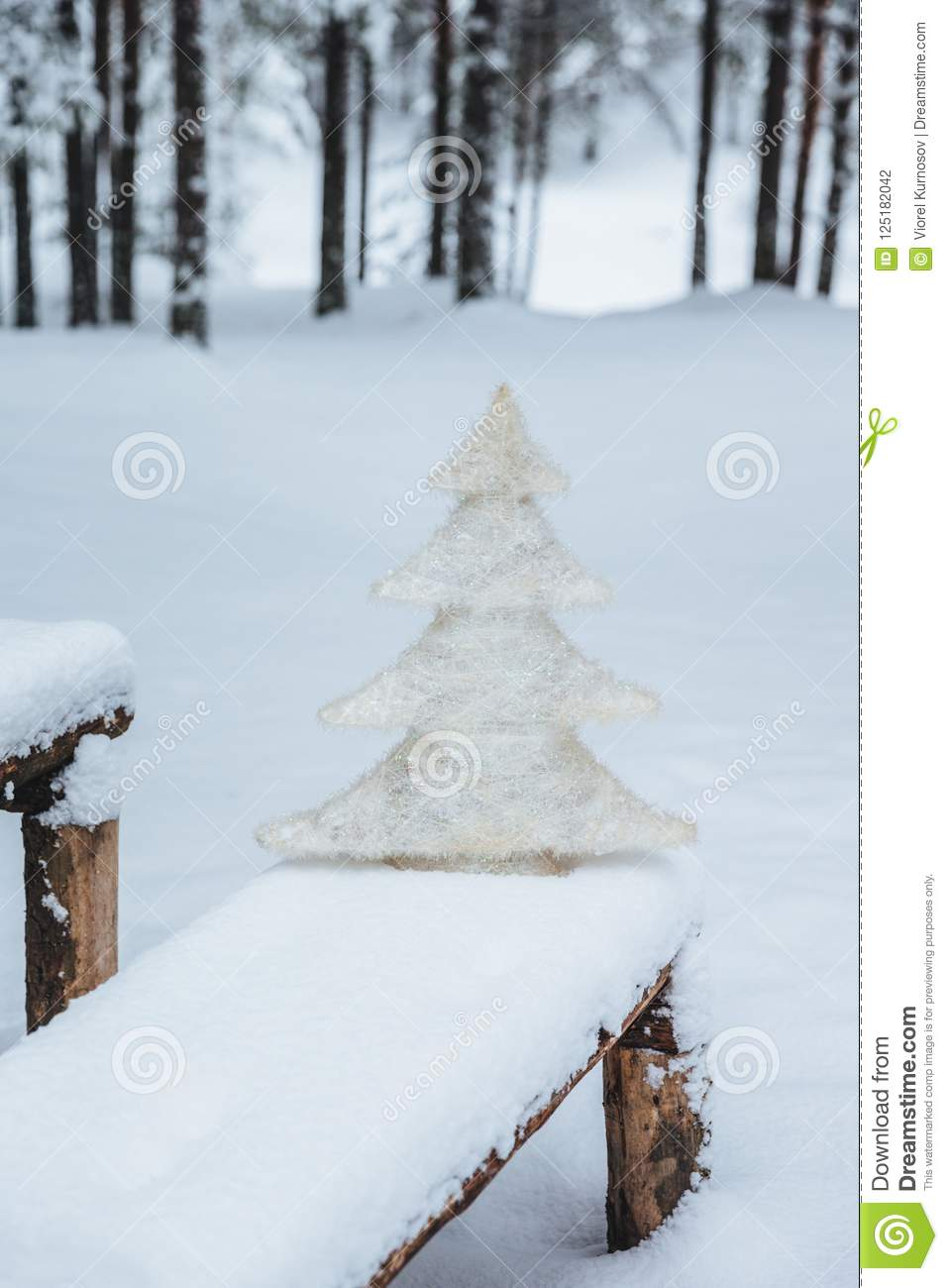 Vertical shot of white artificial fir tree on bench covered with snow, in winter frosty forest. Holidays decoration. Season concep