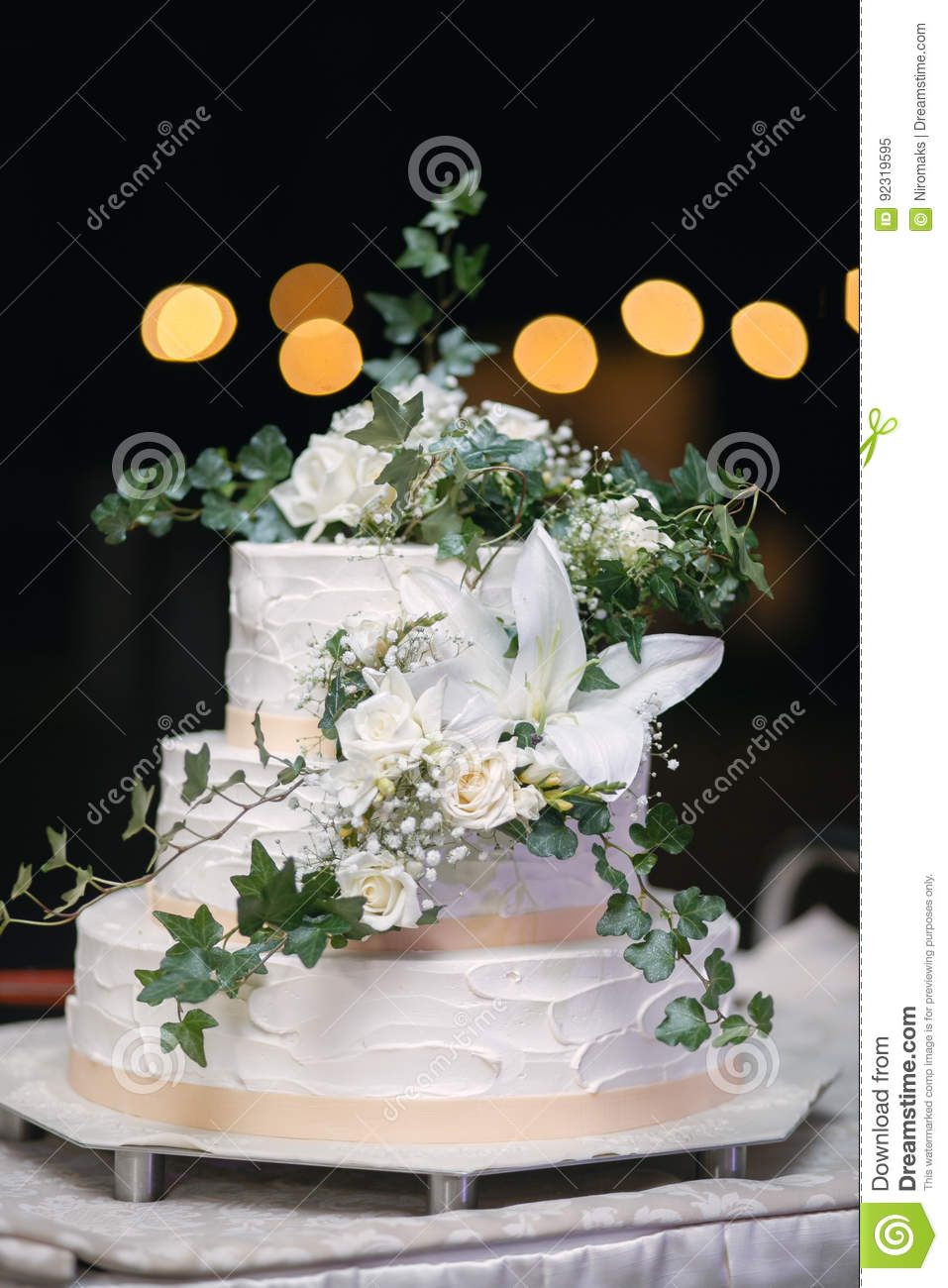 Vertical Shot Of A White Wedding Cake With Fresh Flowers Stock Image