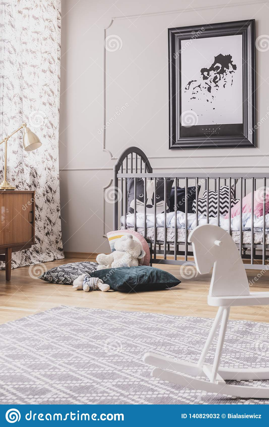 Vertical view of black and white map in frame above wooden crib with pillows, real photo with carpet on the wooden floor