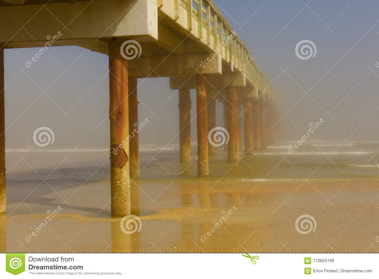 Long wooden pier stretching out to a foggy ocean horizon
