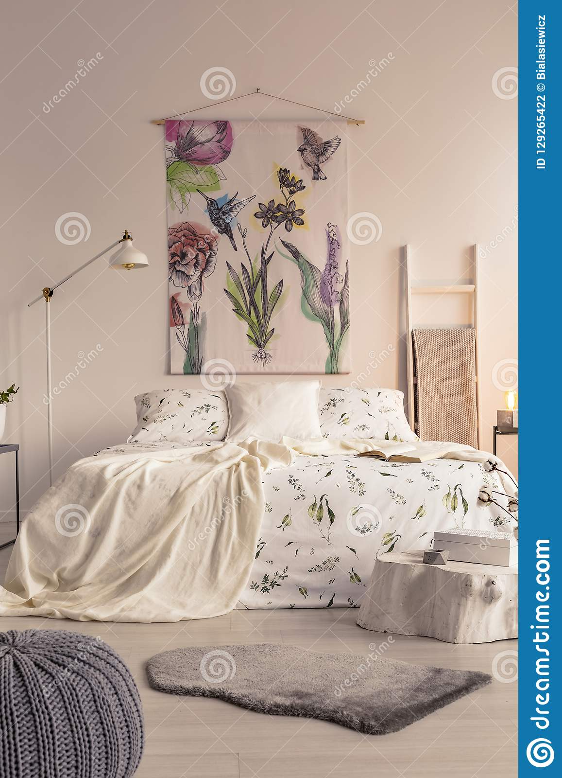 Vertical view of a pastel bedroom interior with a big bed in the middle and a painted fabric art on the wall