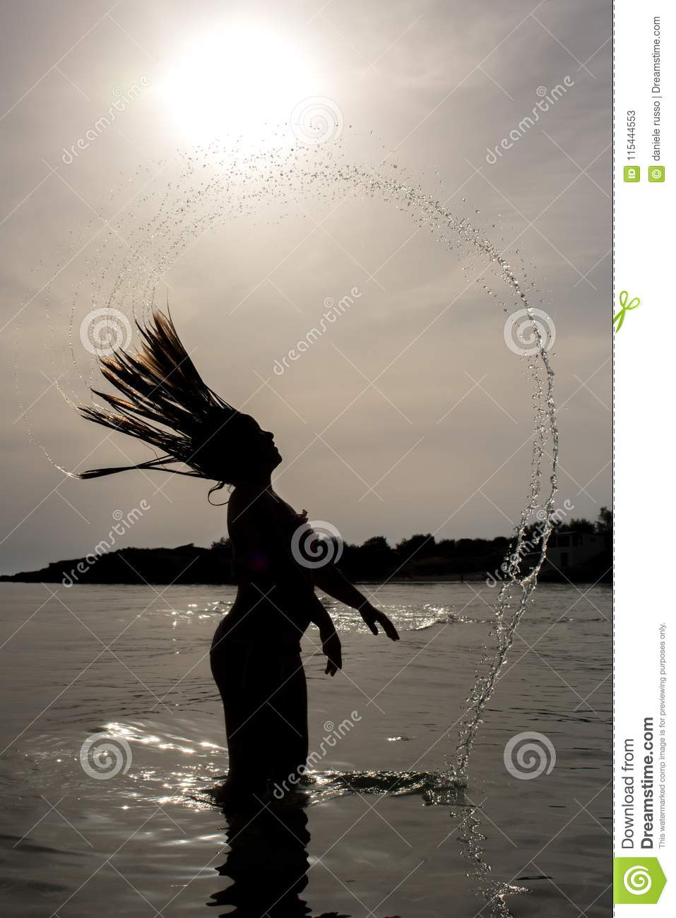 Vertical View of a Silhouette of a Young Girl Splashing the Water with Hair in the Sea on Sun Backlight in a Foggy Day