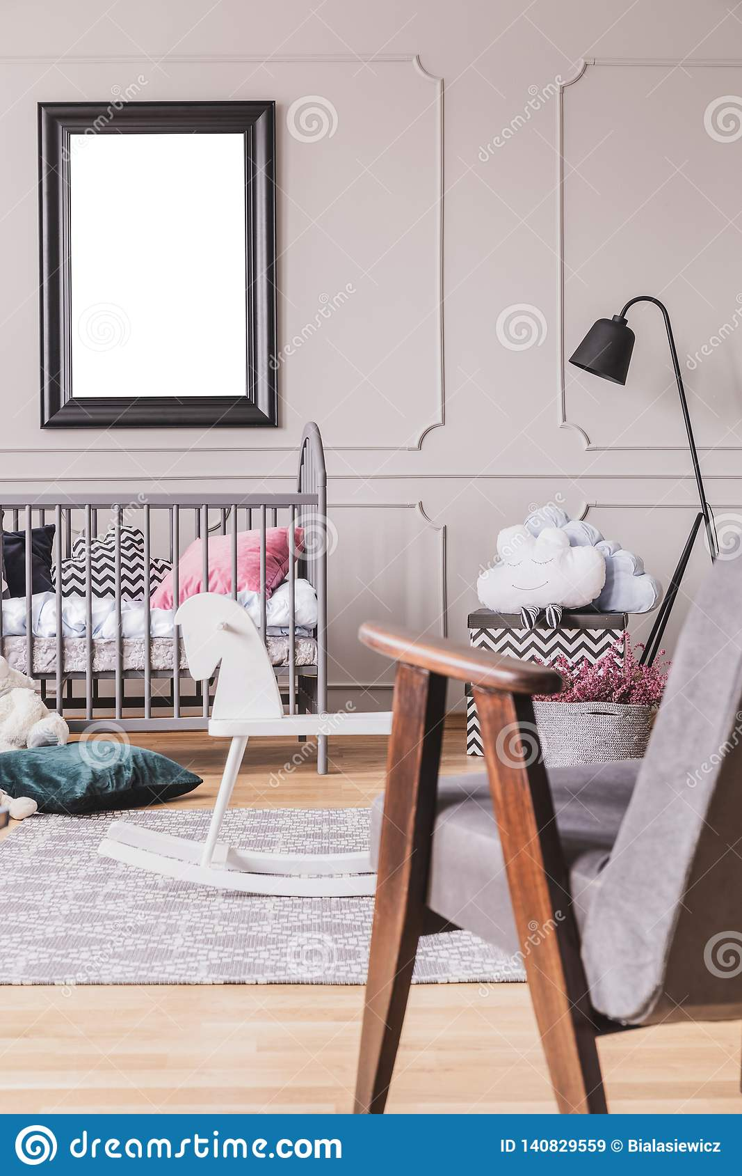 Vertical view of vintage grey armchair in trendy mid century baby room interior with mockup in black frame on the empty grey wall