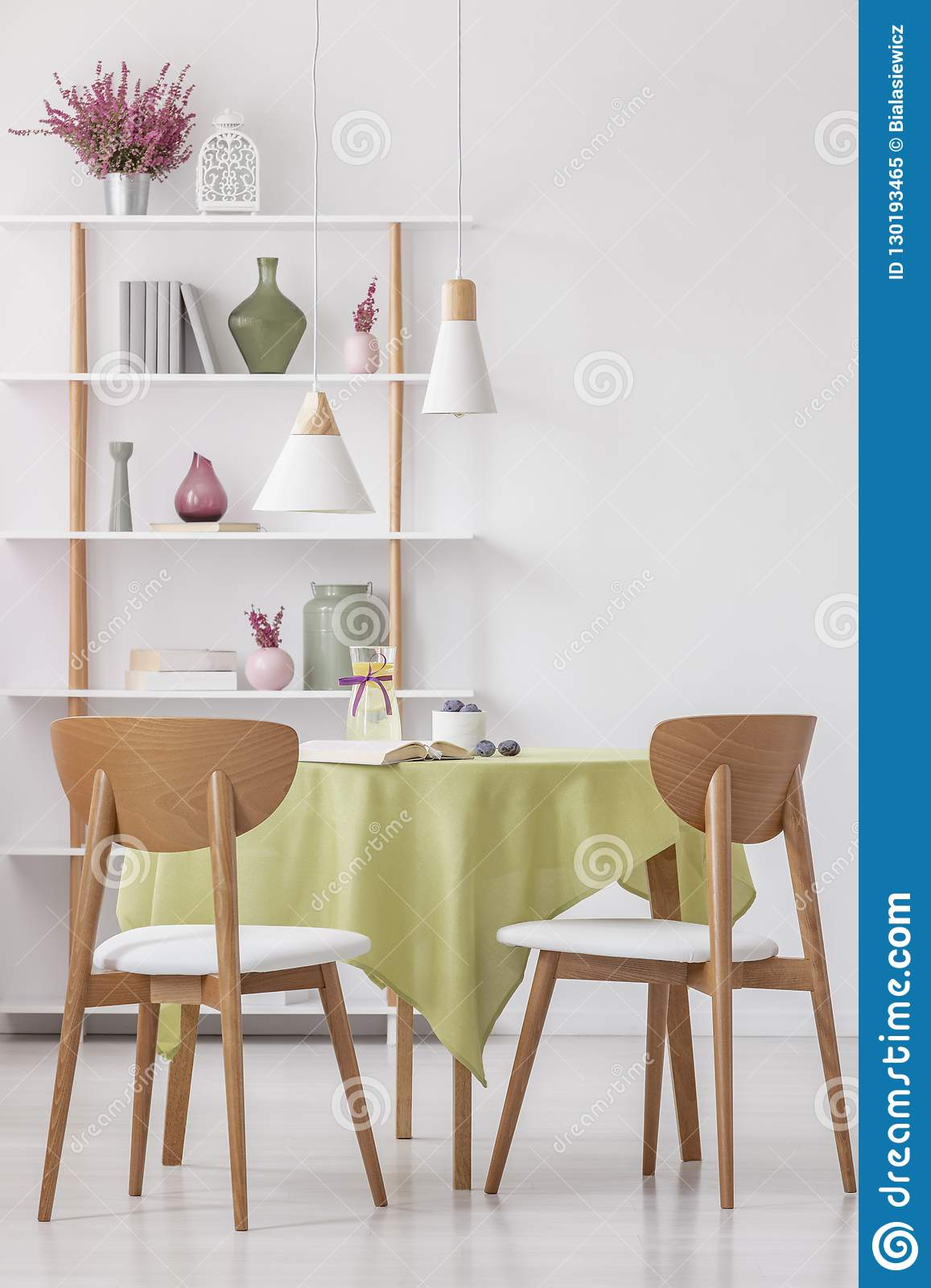 Wooden Chairs At Round Table With Olive Green Tablecloth In Bright