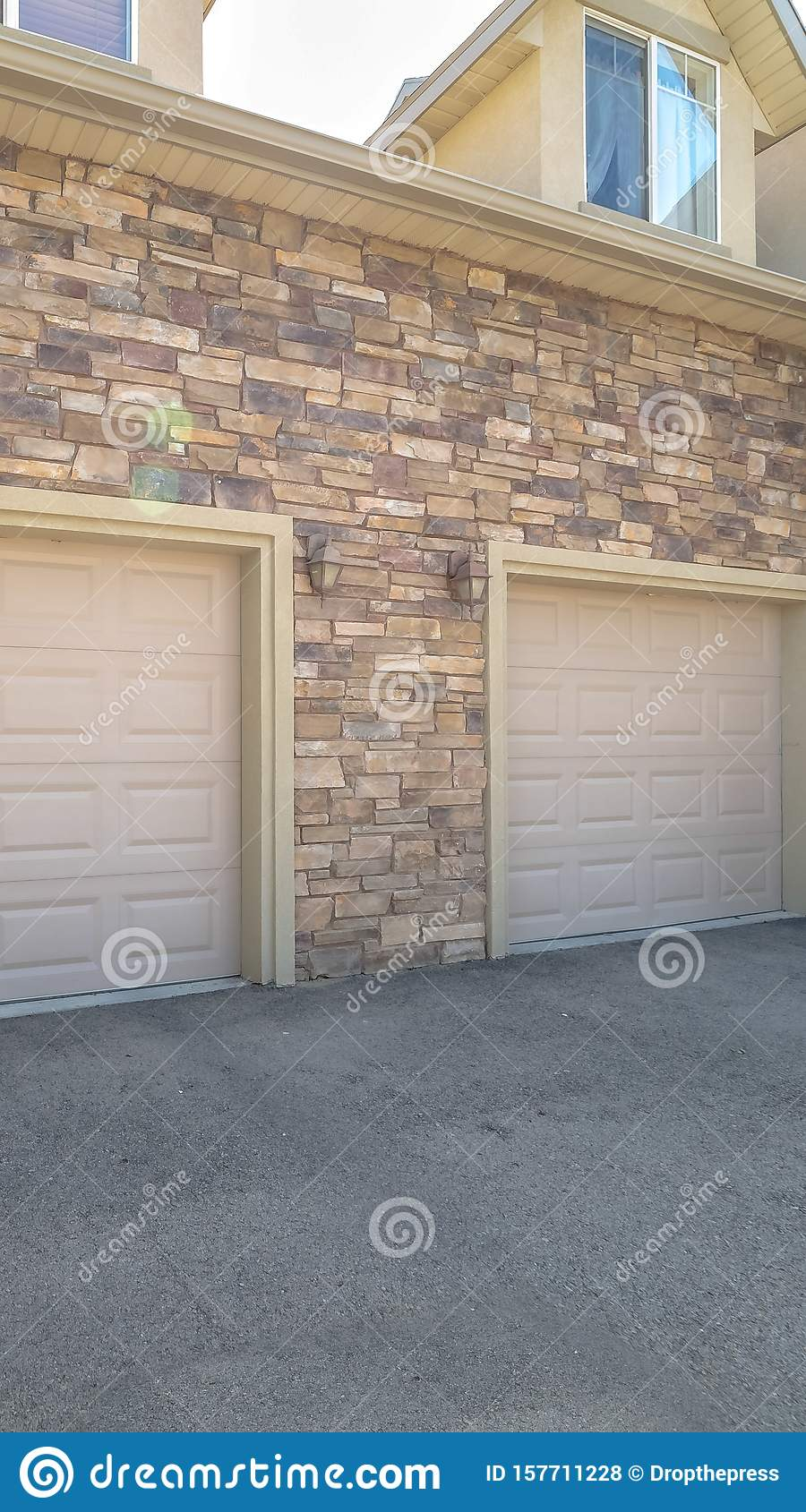 Vertical White Garage Doors Of A Home Against Exterior Wall Covered With Stone Bricks Stock Photo Image Of Garage Door 157711228