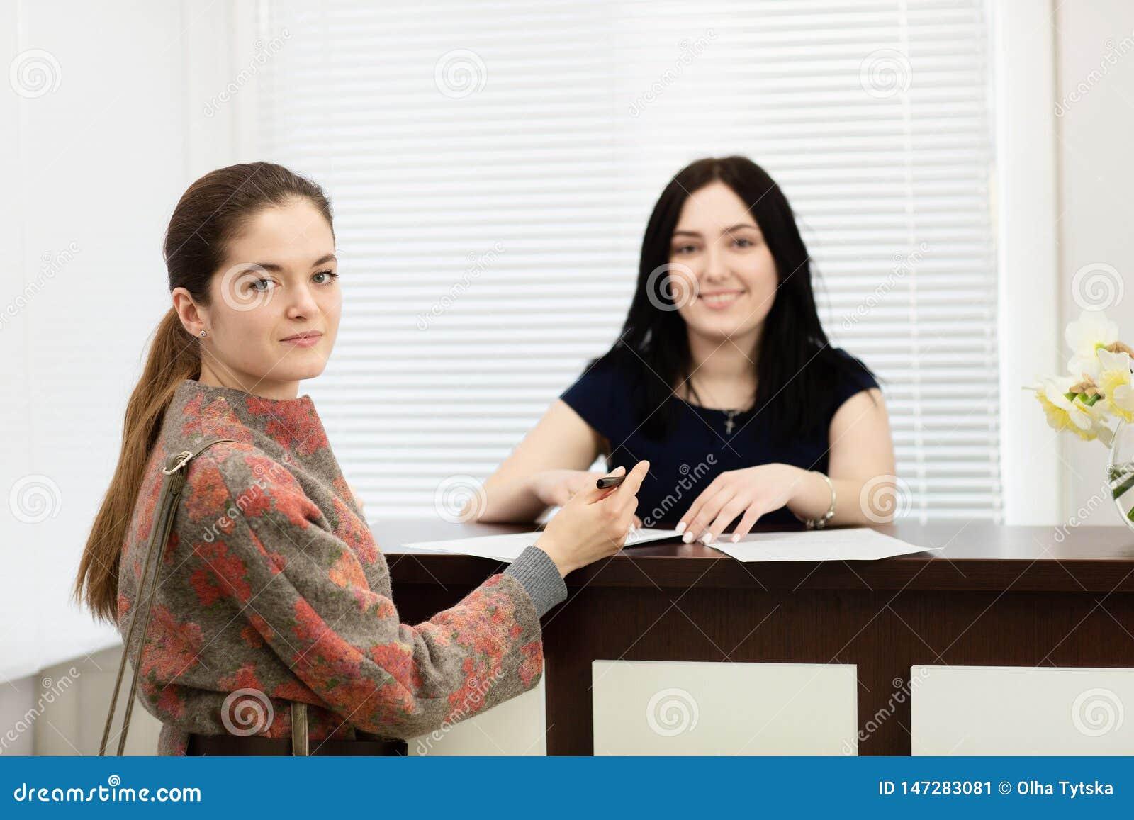 Verticale de deux jeunes femmes de sourire Administrateur de clinique dentaire et patient