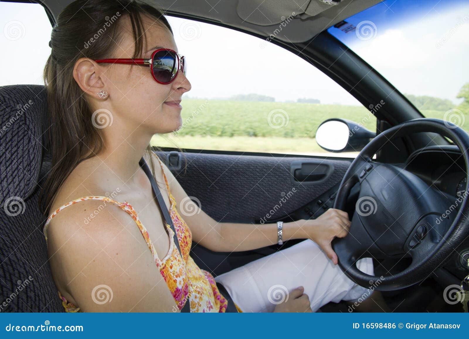 Verticale de la jeune femme de sourire conduisant le véhicule
