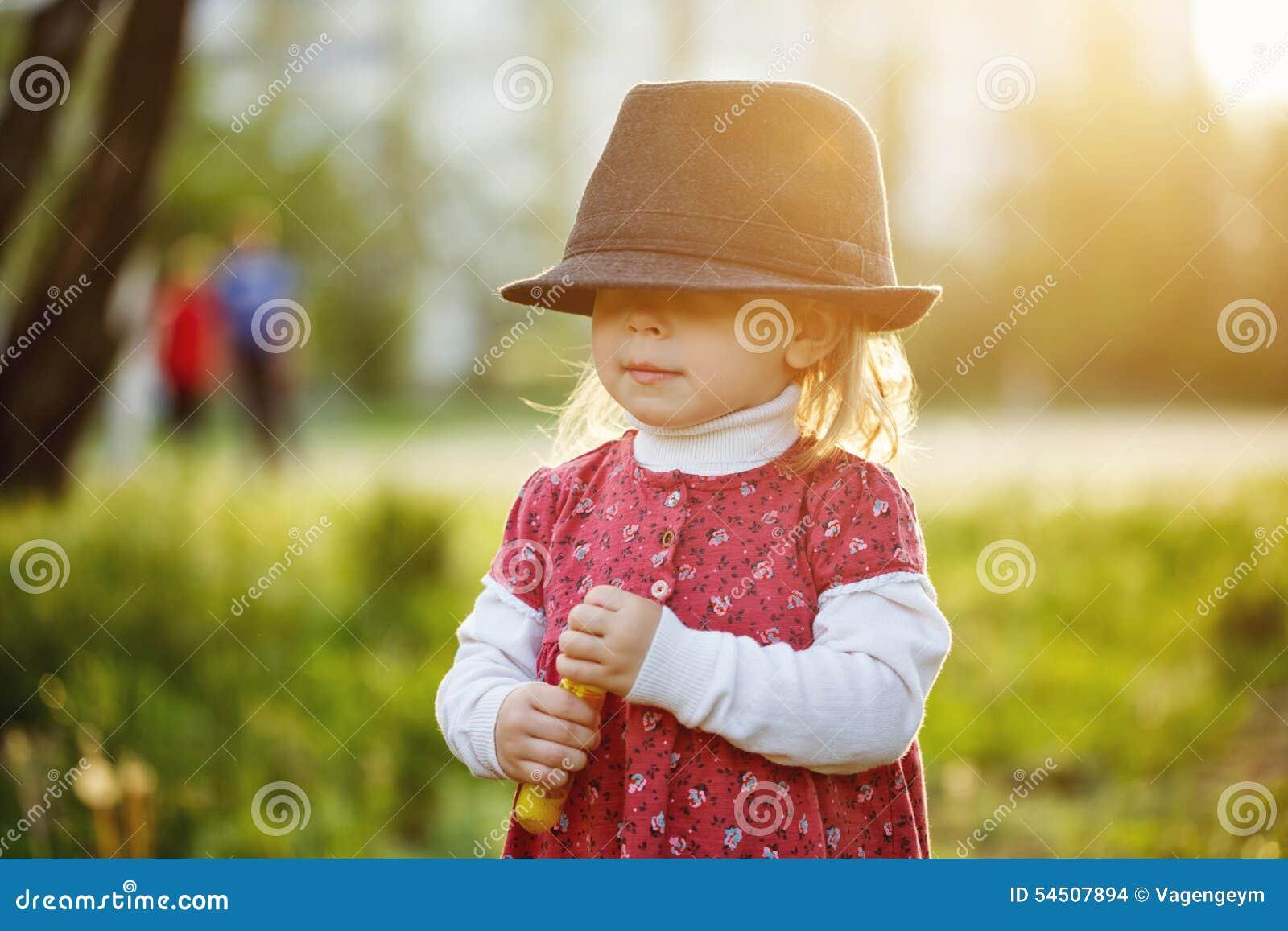 Verticale de petite fille mignonne dans le chapeau Ressort