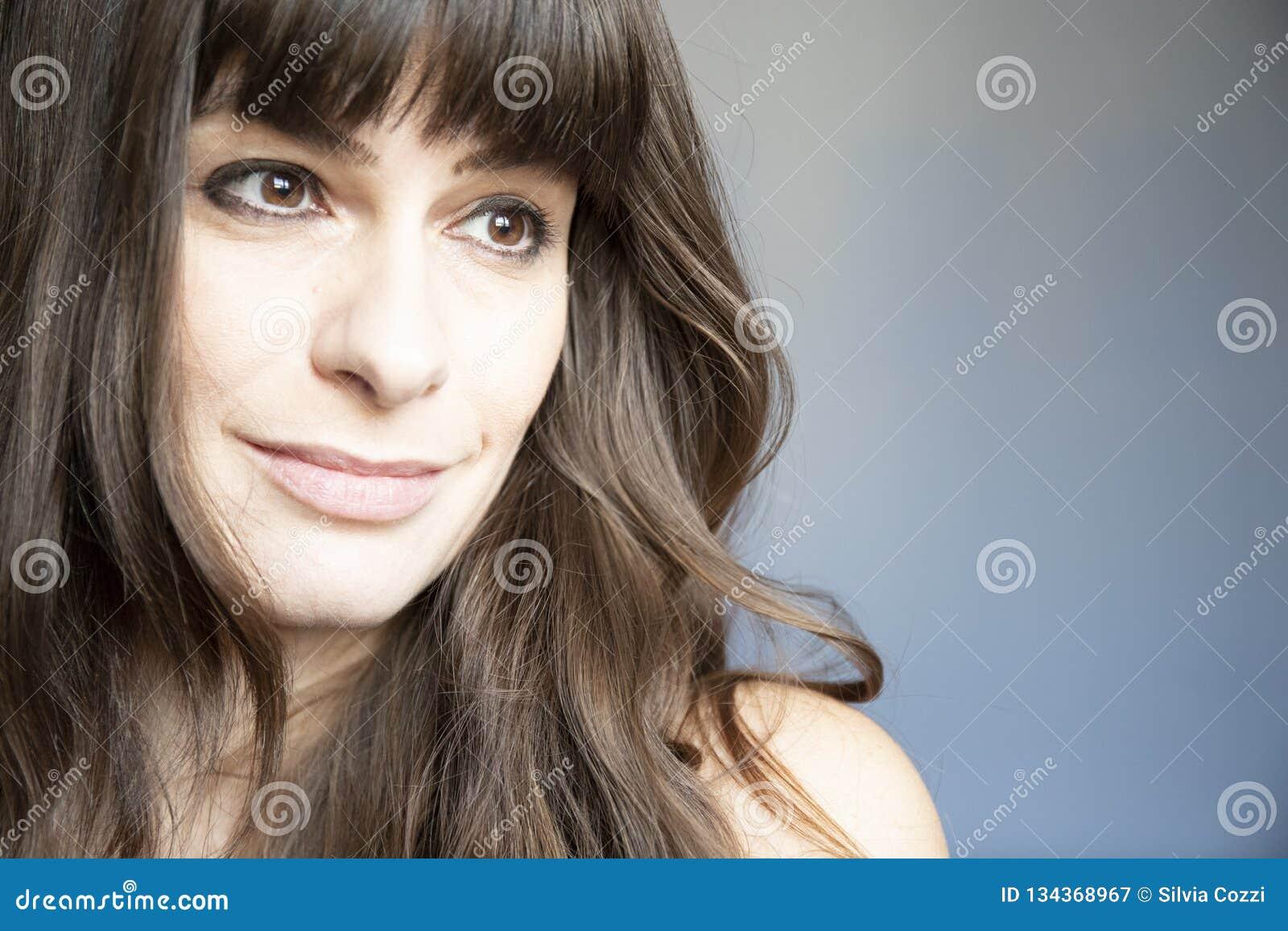 Verticale de plan rapproché de jeune femme Caucasien avec de longs cheveux bruns et coups