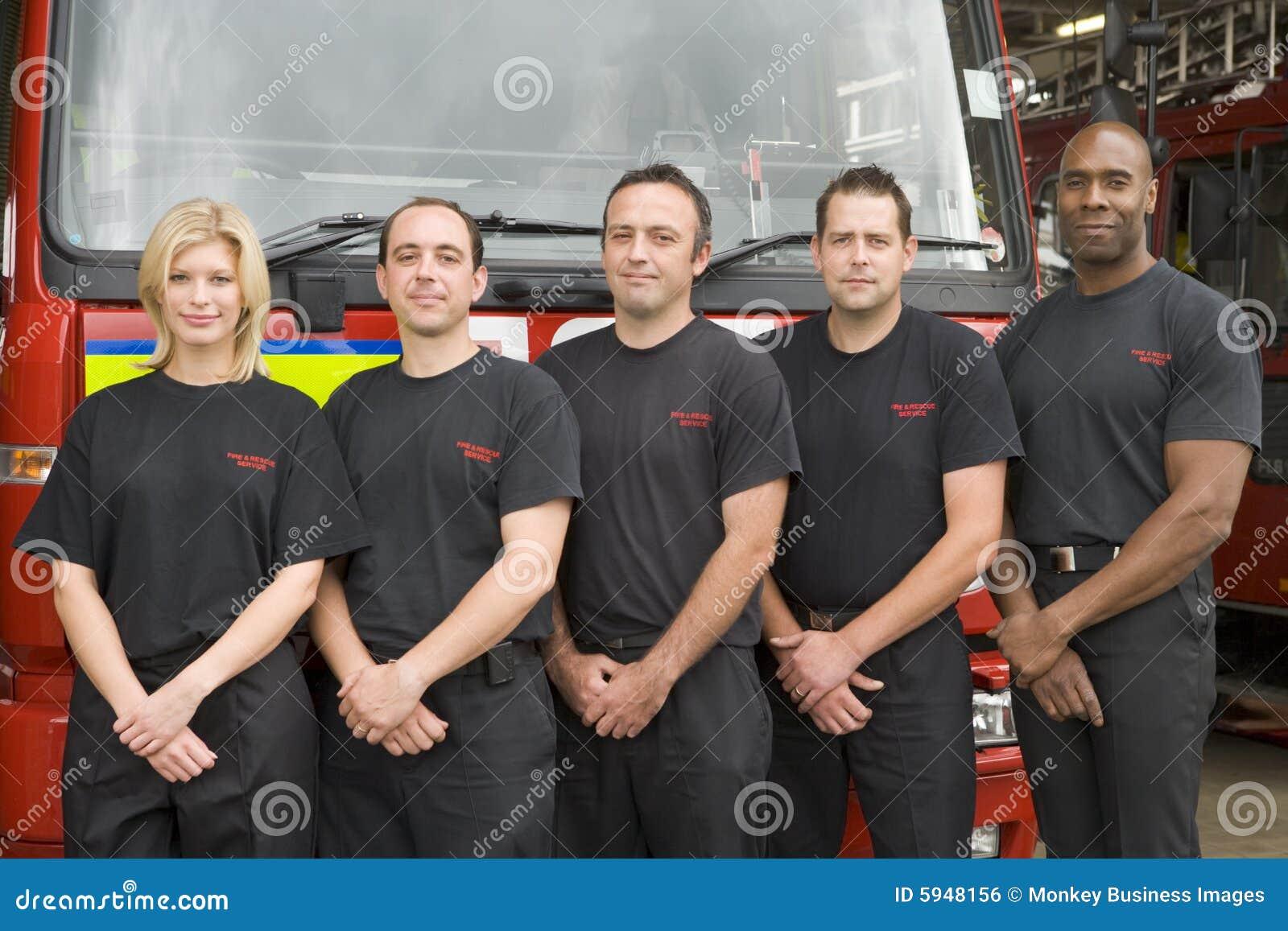 Verticale des sapeurs-pompiers se tenant prêt une pompe à incendie