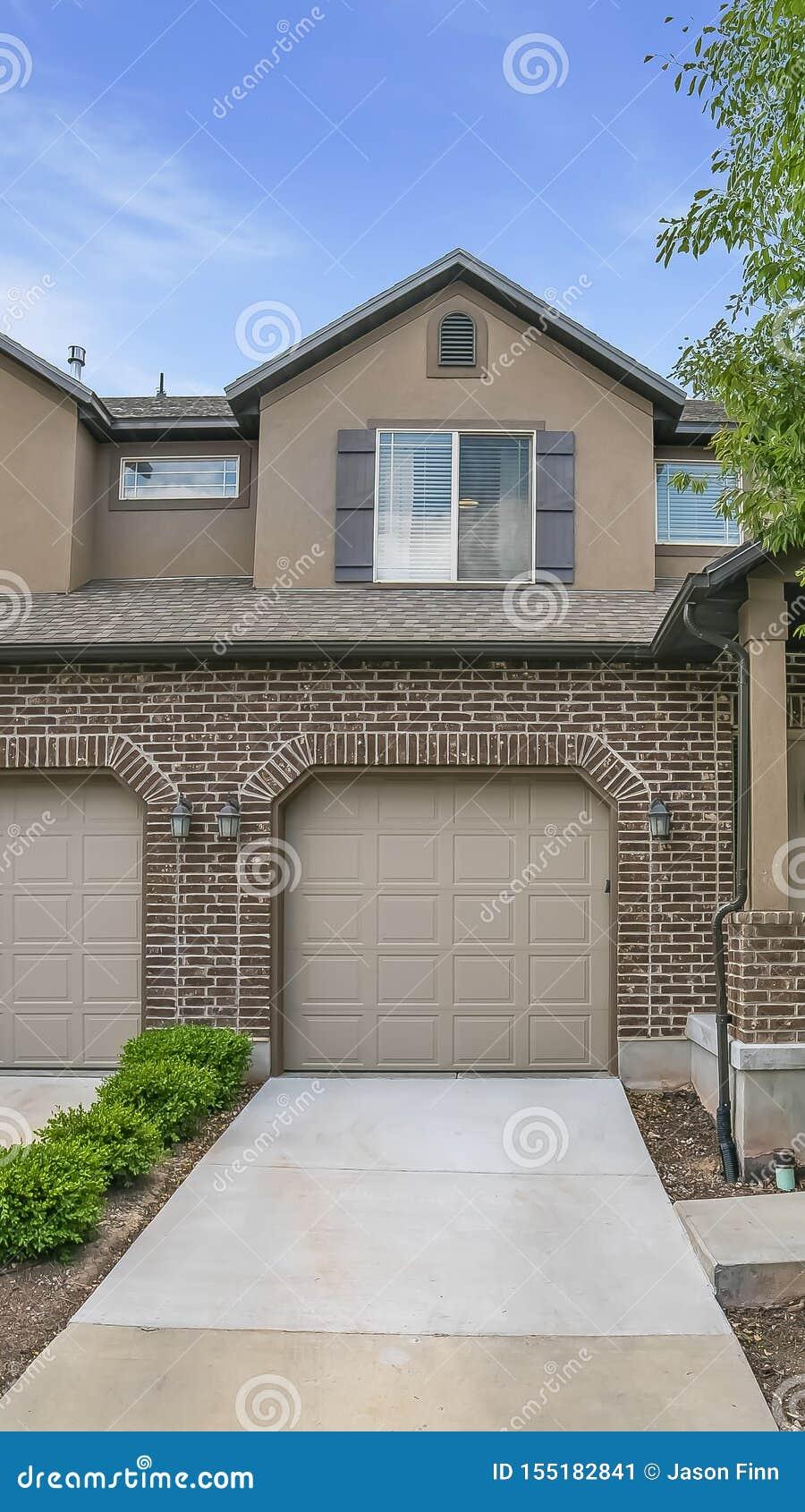 Verticale die kaderyard en portiek bij de voorgevel van een huis met bakstenen muur en zoldervensters wordt bekeken