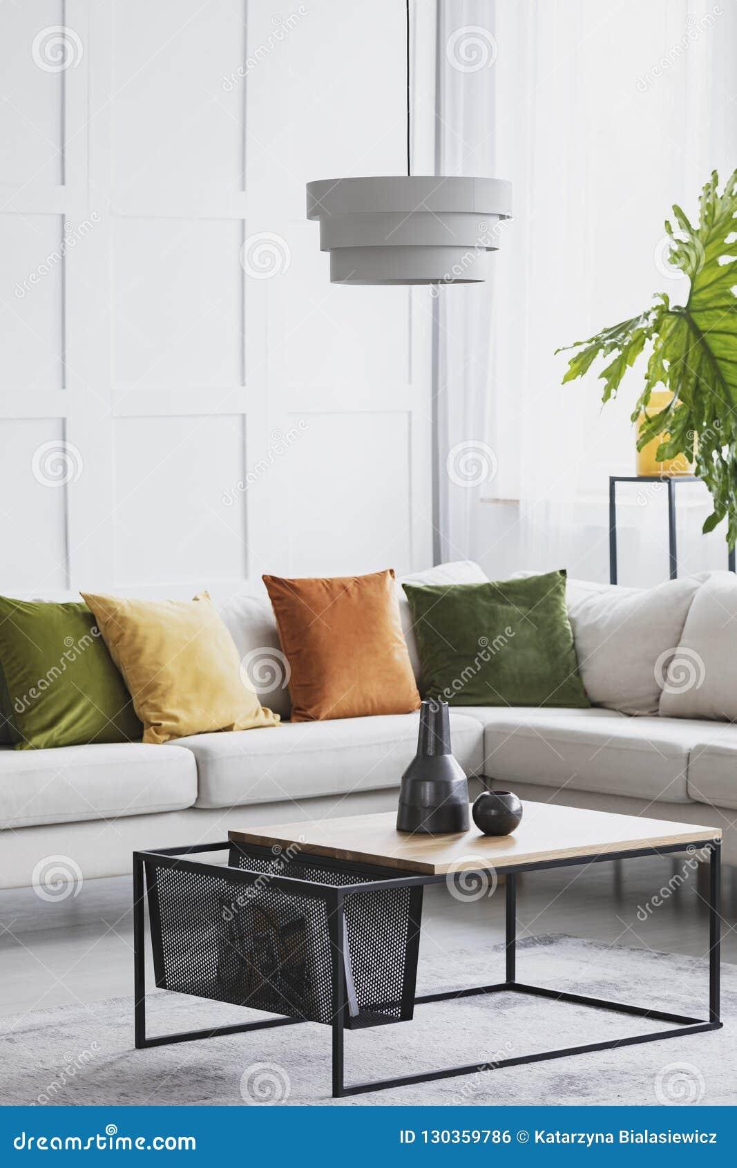 Verticale mening van het eenvoudige witte kroonluchter hangen boven moderne houten koffietafel in woonkamer met gouden kalkaccent