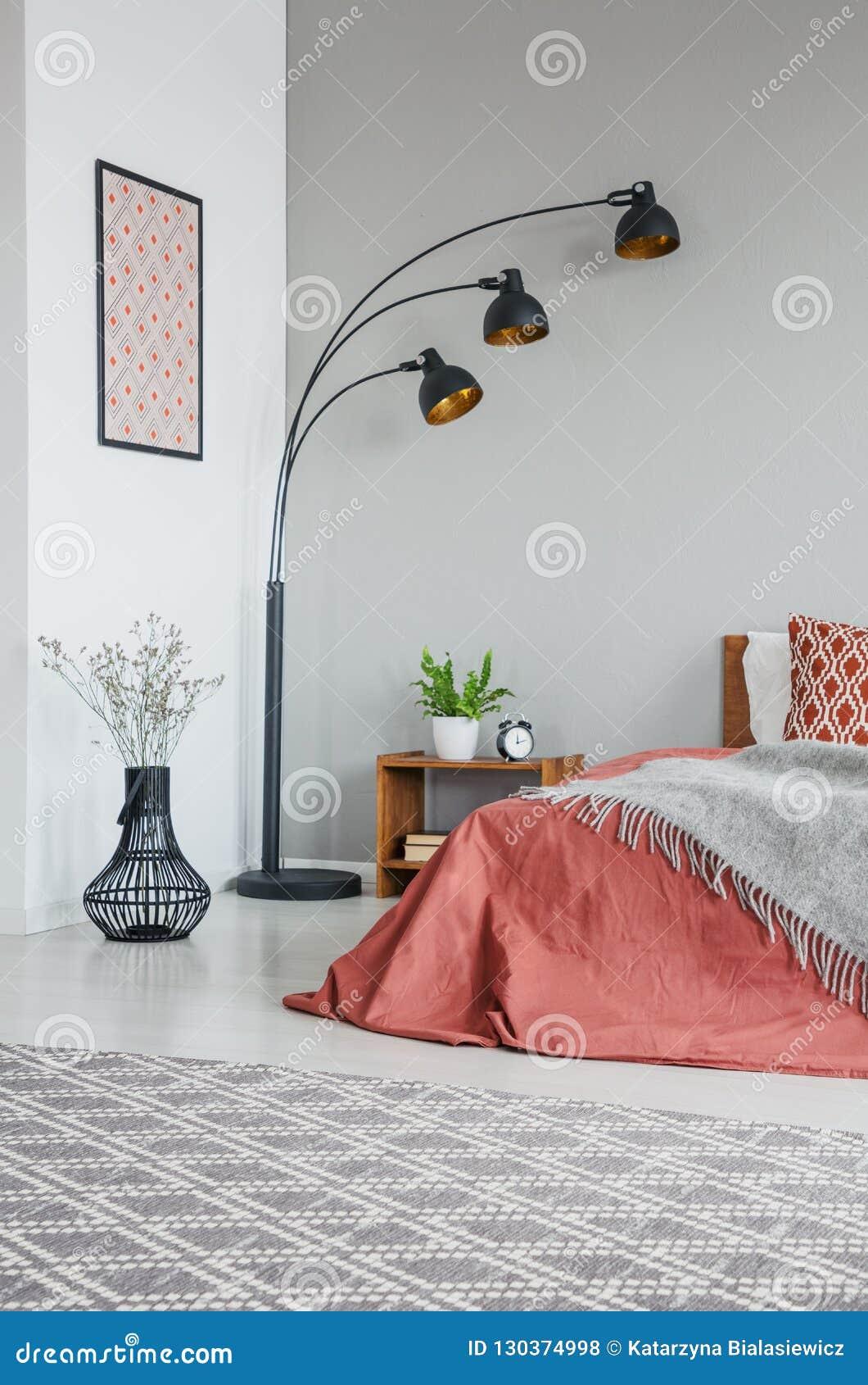 Vertikal sikt av den gråa filten på säng med kuddar i sovruminre med lampan och växter