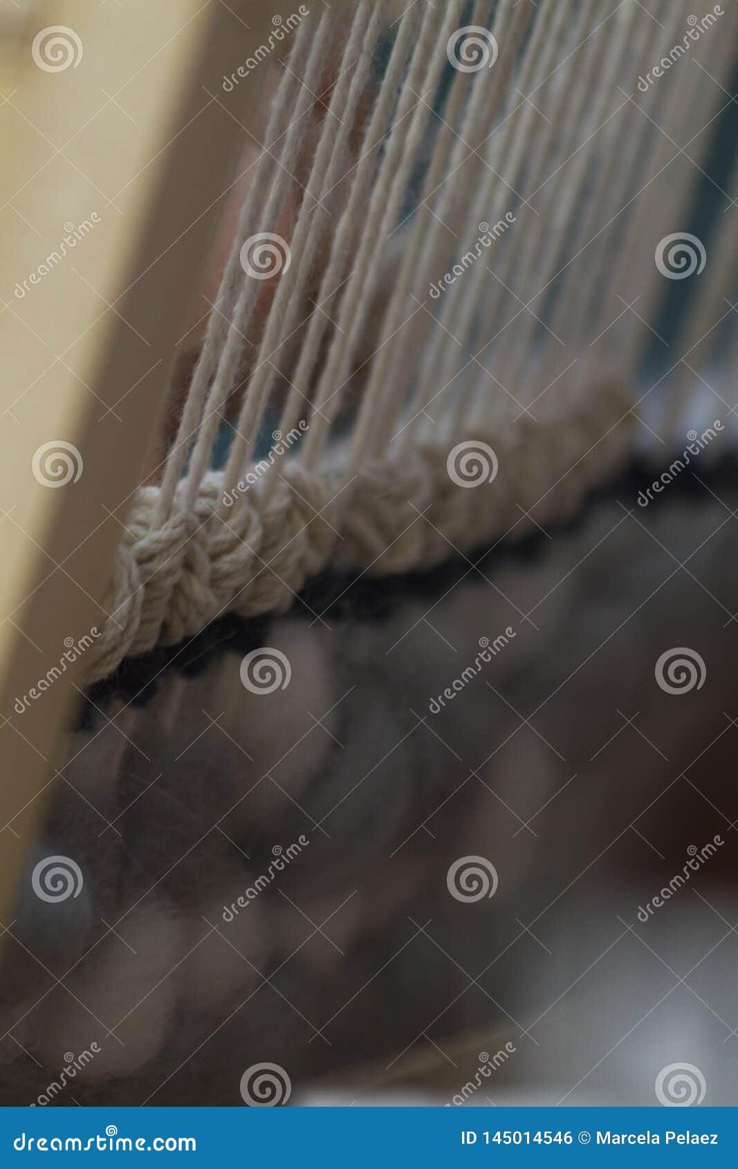 Vertikale Tapisserienahaufnahme mit beige Faden