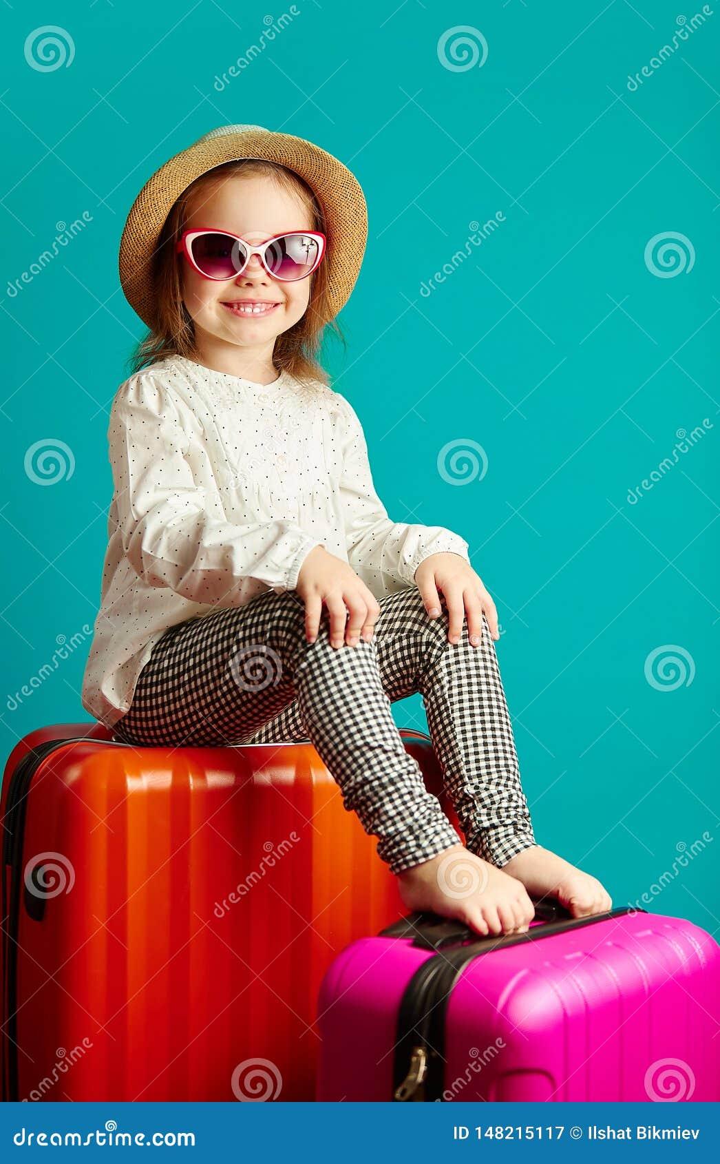 Vertikaler Schuss von lächeln wenig Mädchen im Strohhut und in Sonnenbrille, die auf Koffern, Porträt schönes Kinderdes gehens si