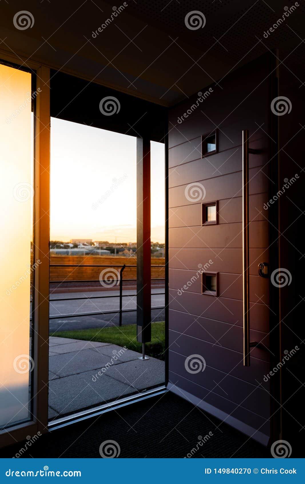 Vertikalt skott av en bred öppen modern främre foor som visar fält, och en solnedgång i avståndet