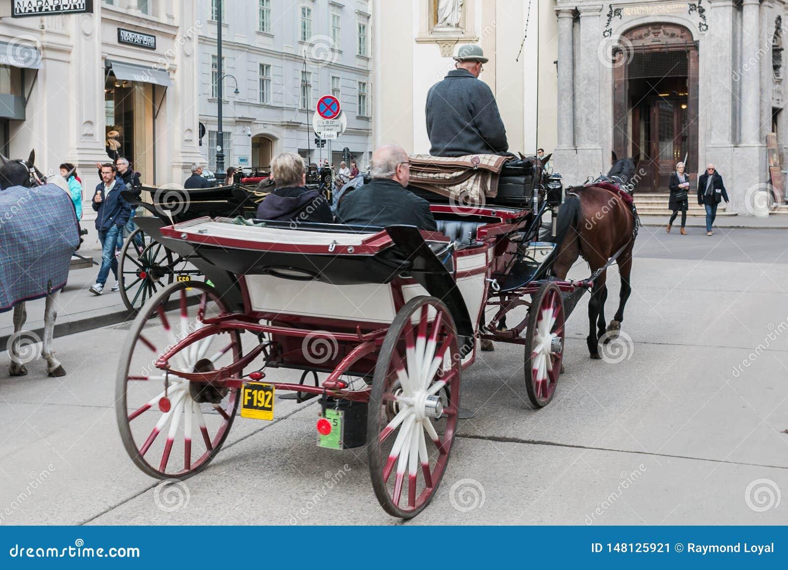 Vervoer met paarden, bestuurder en toeristen in Wenen op een sightseeingsreis rond de stad