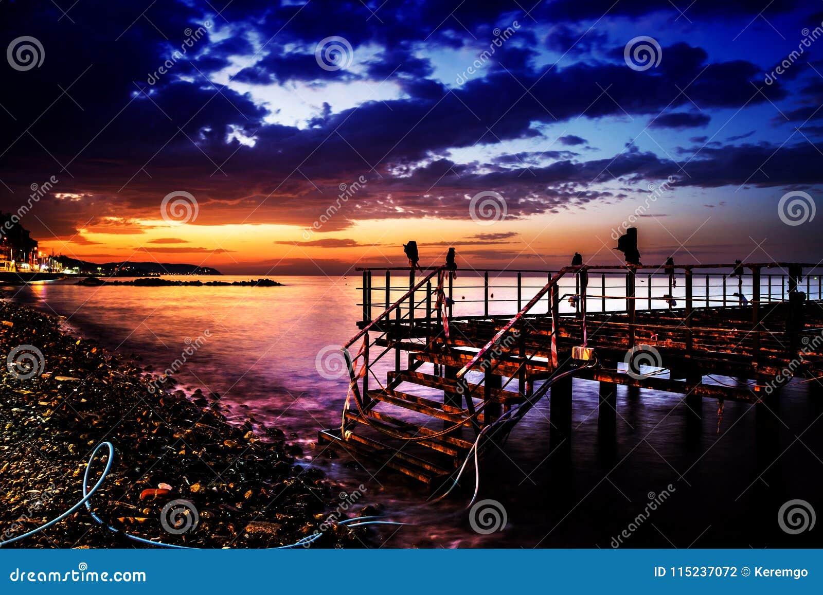 Verwüstetes Dock auf Sonnenuntergang mit ruhigem See