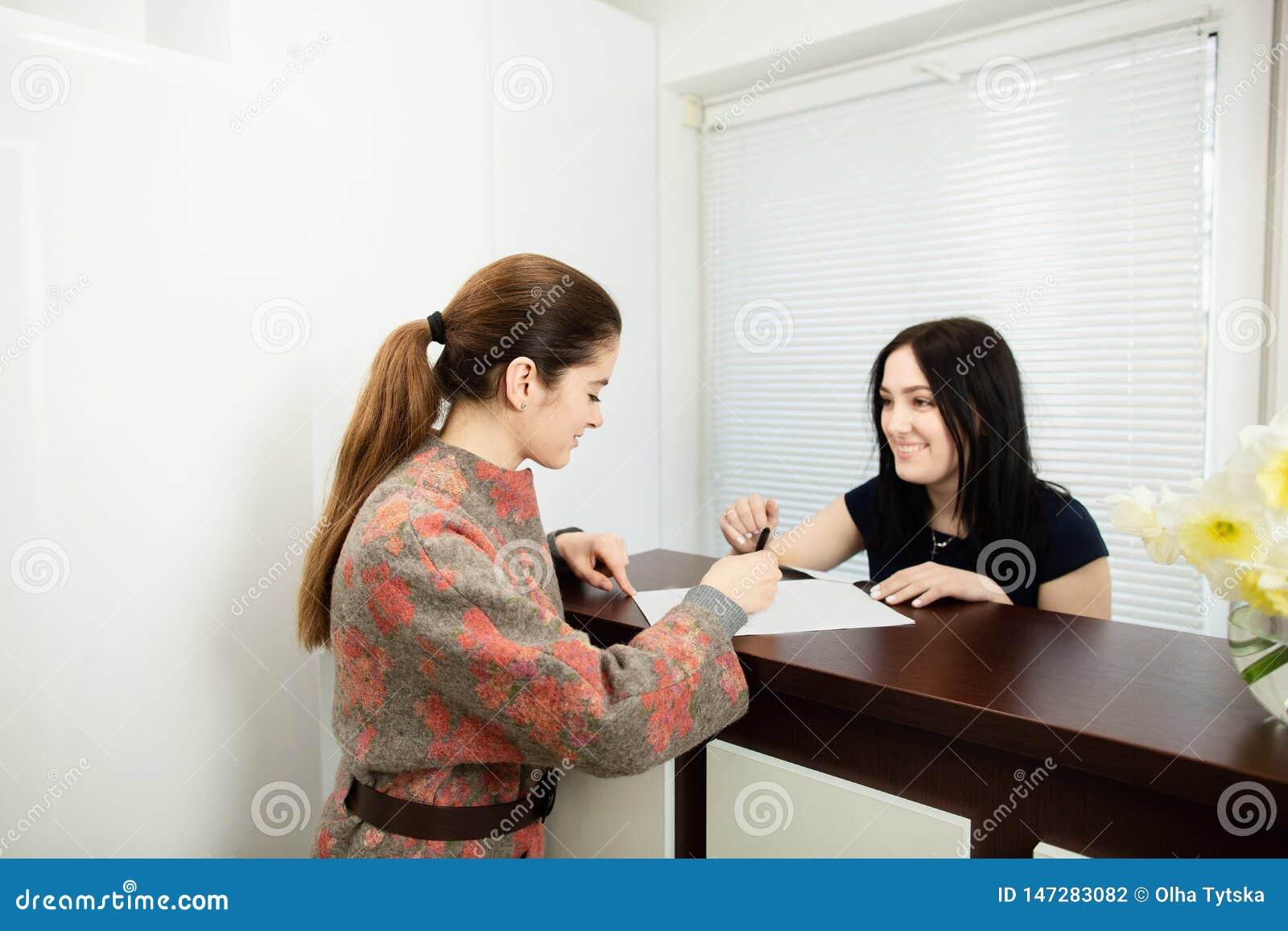 Verwalter der jungen Frau in einer zahnmedizinischen Klinik an dem Arbeitsplatz Aufnahme des Kunden