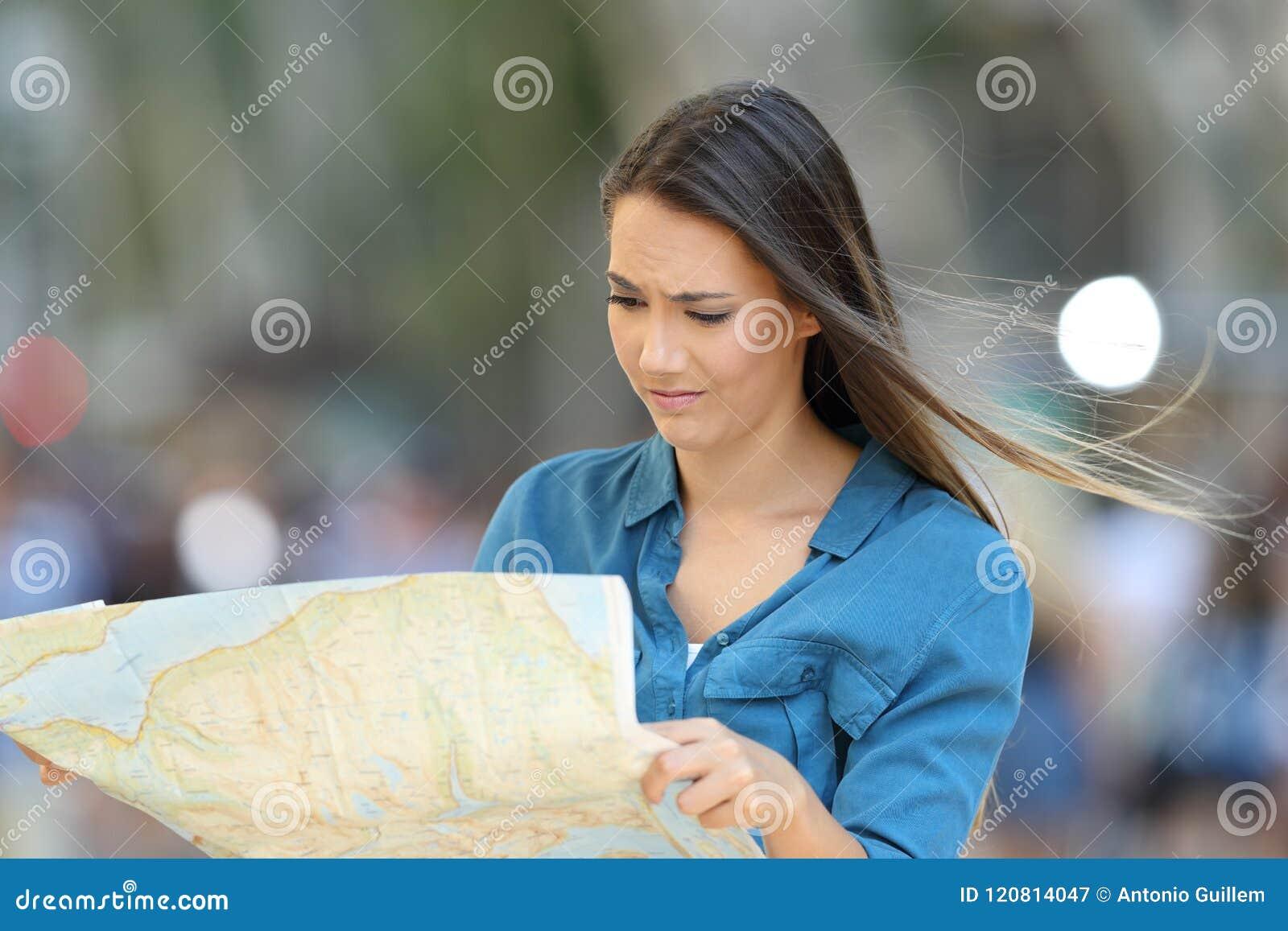Verwarde verloren toerist die een kaart lezen die plaats zoeken
