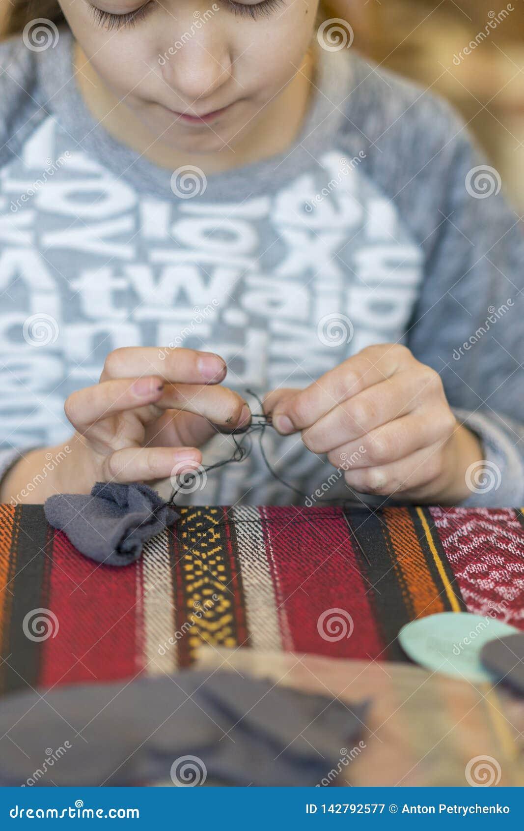 Verwezenlijking het meisje naait stuk speelgoed dat van gevoeld wordt gemaakt Het meisje naait een grijze muis Het meisje naait e