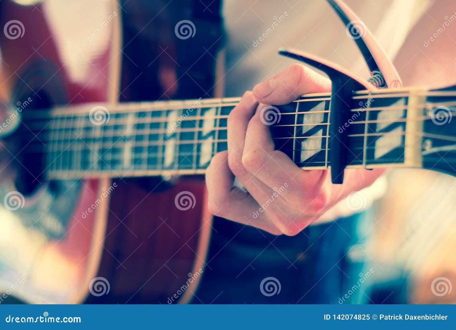 Verwijderd van een jonge mens die een zonnestraal westelijke gitaar spelen