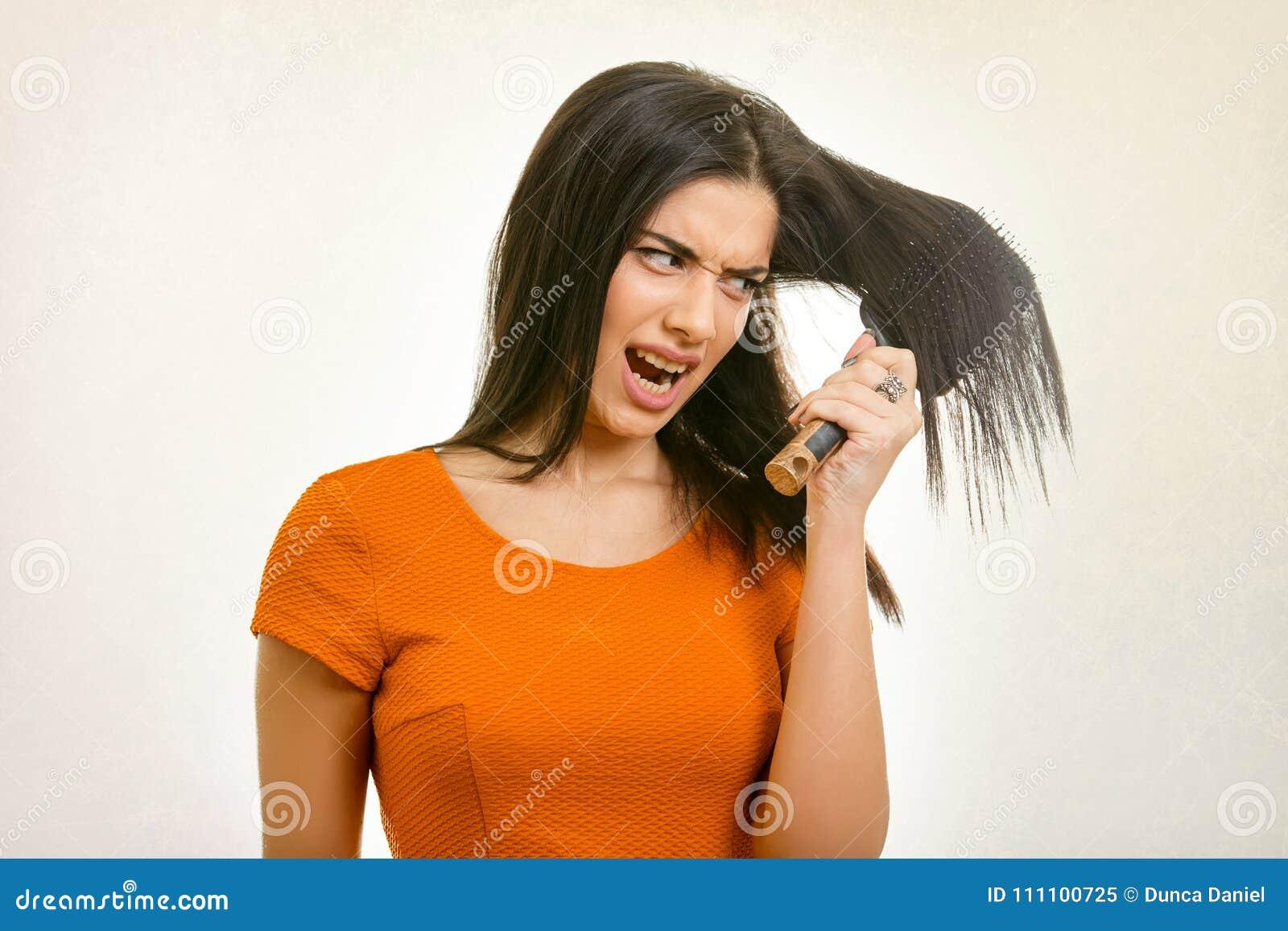 Verwirrtes unordentliches Frisurproblem Frau, die ihr schädigendes Haar bürstet