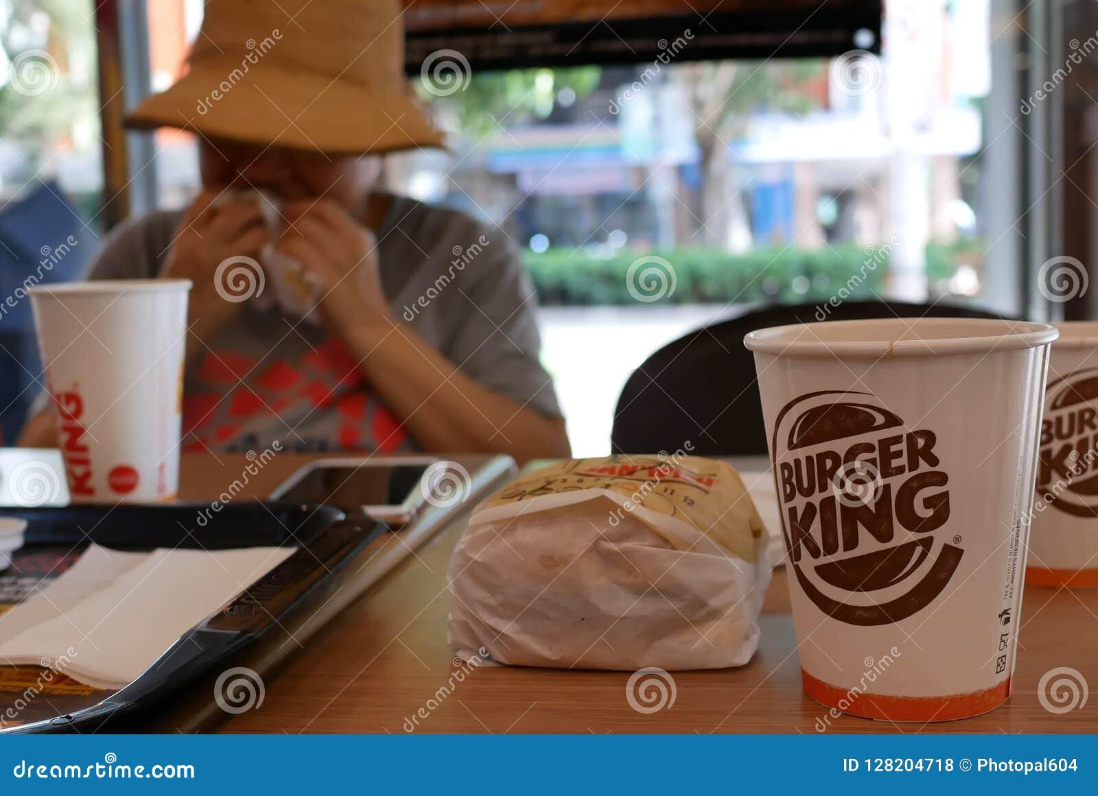 Verwischen Sie die Bewegung der Frau Burger essend und heißen Kaffee an Burger King-Schnellrestaurant trinkend