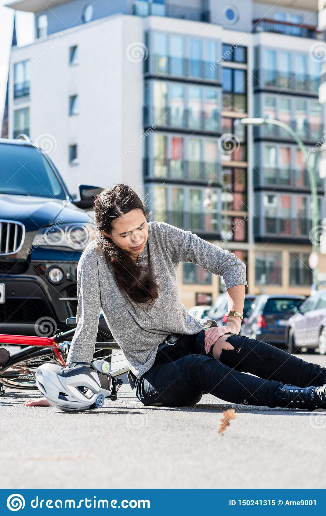 Verwonde vrouw met strenge die pijn door knieverstuiking wordt veroorzaakt na fietsongeval