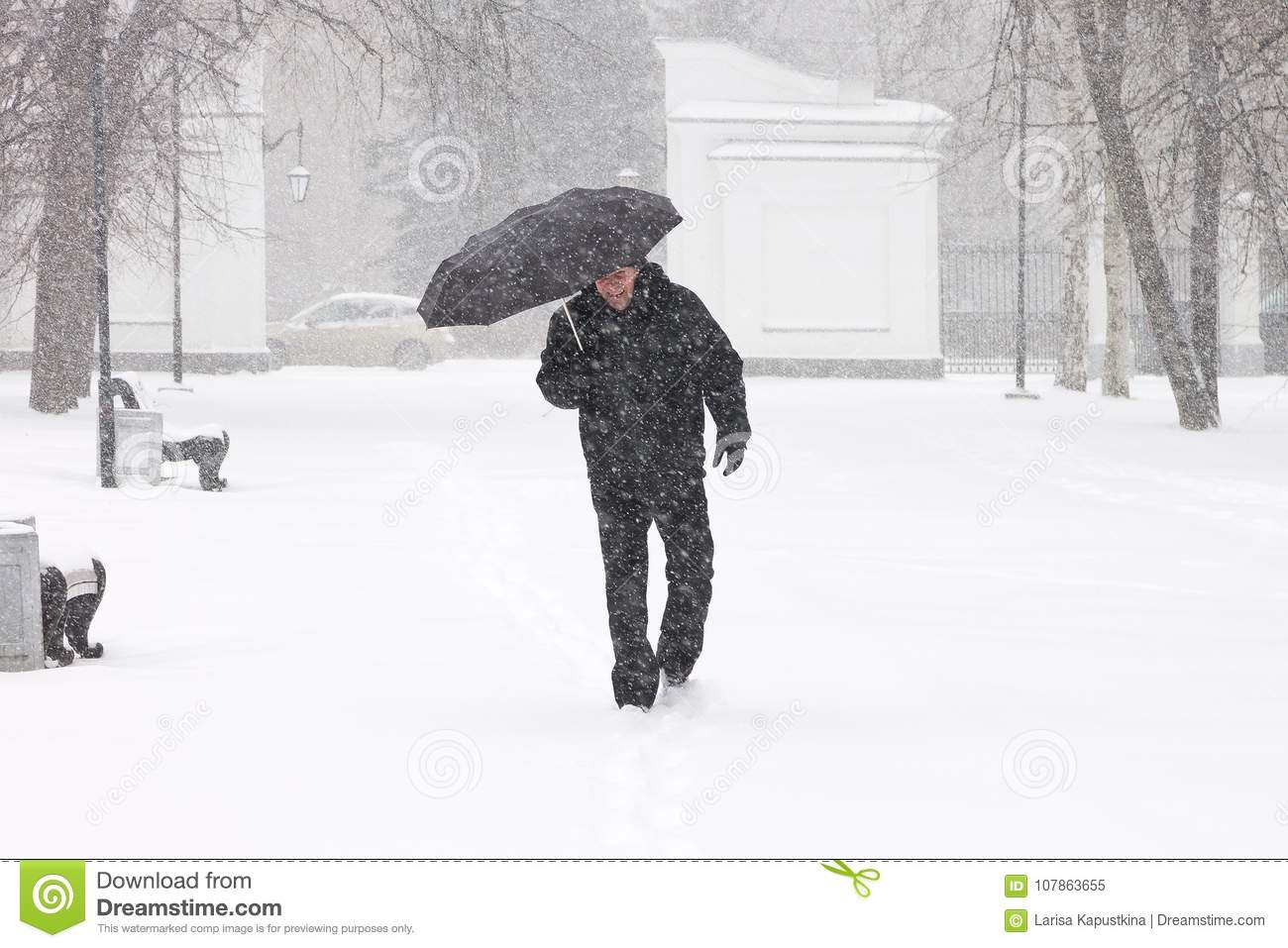 Very bad weather in a city in winter: terrible heavy snowfall and blizzard. Male pedestrian hiding from the snow under umbrella