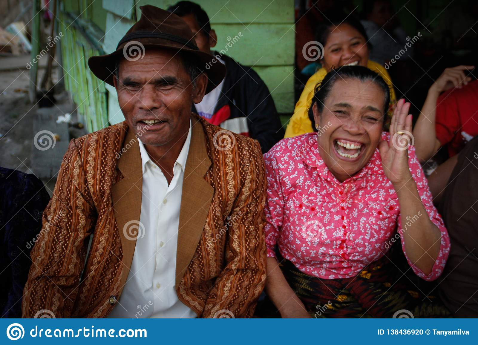 very cheerful laughing and fumbling Indonesian elderly woman in a pink blouse and her stylishly dressed man in a brown hat